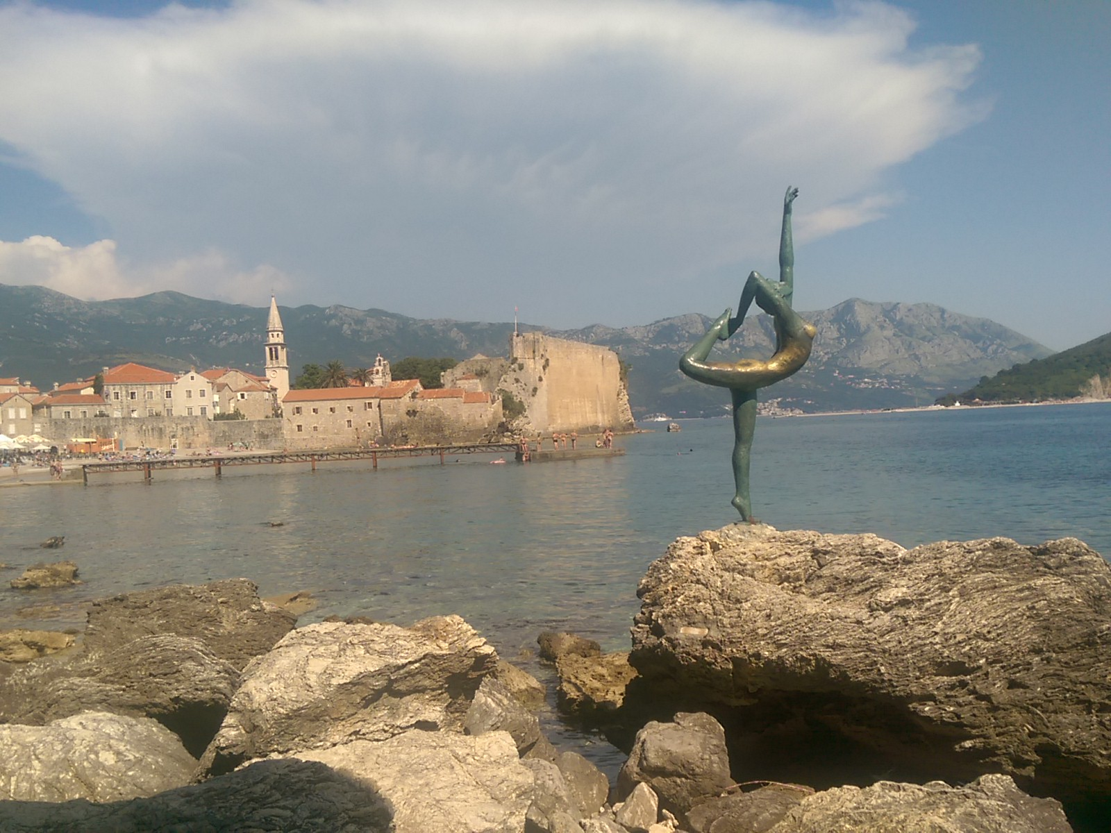 A green and gold statue of a woman doing the dancer pose on a rock, with distant mountans and a stone old town with city walls and churches in the background