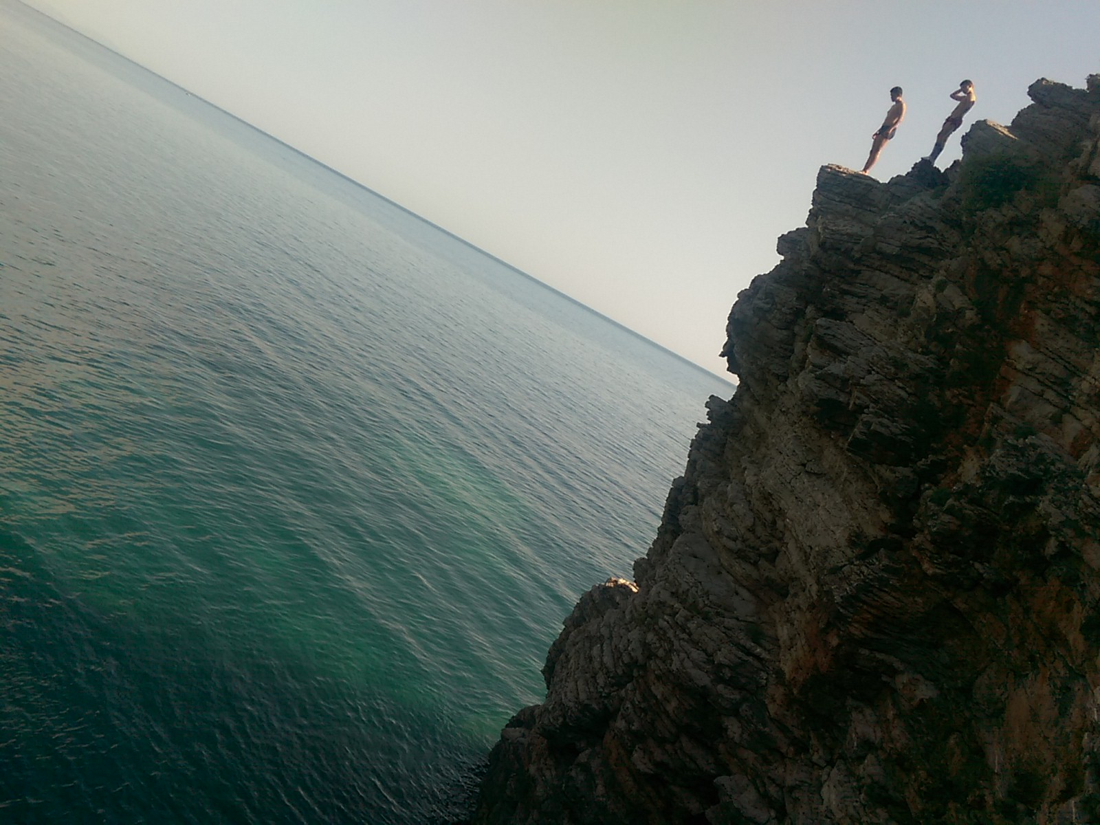 Wide bluegreen sea beyond a cliff the height of a two storey house, with two preteen boys standing at the top