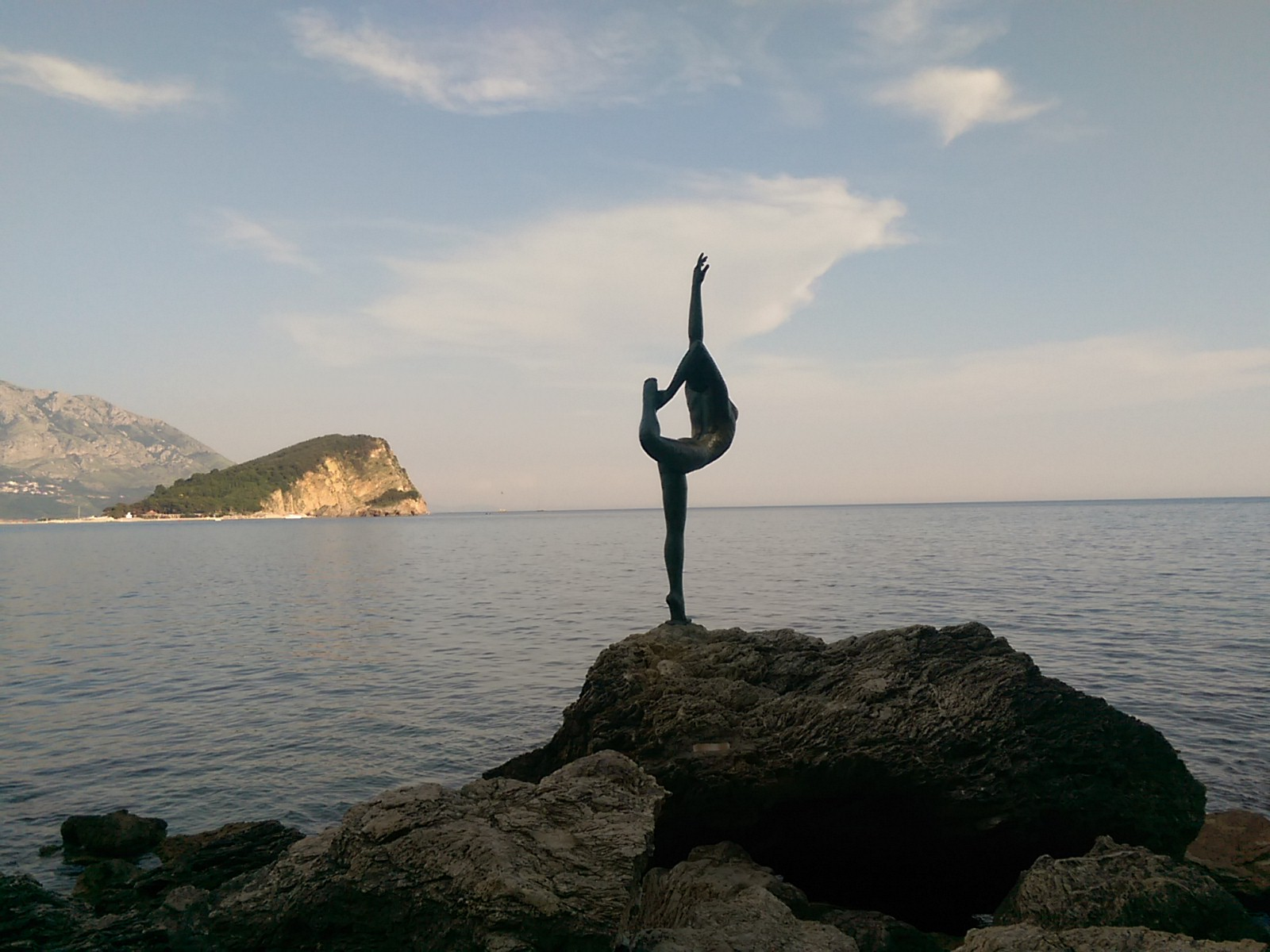 A statue of a woman doing the dancer pose on a rock silhouetted against blue sea and sky with an island to the left