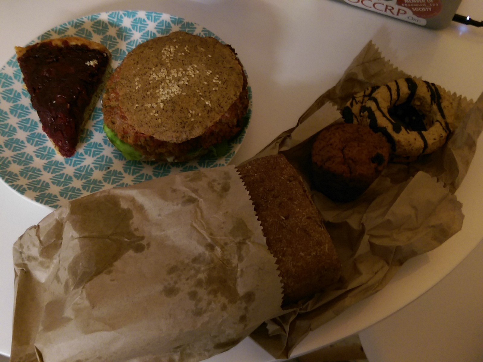 Pie and a burger on a plate from above, next to a loaf of bred in a brown paper bag and cookies
