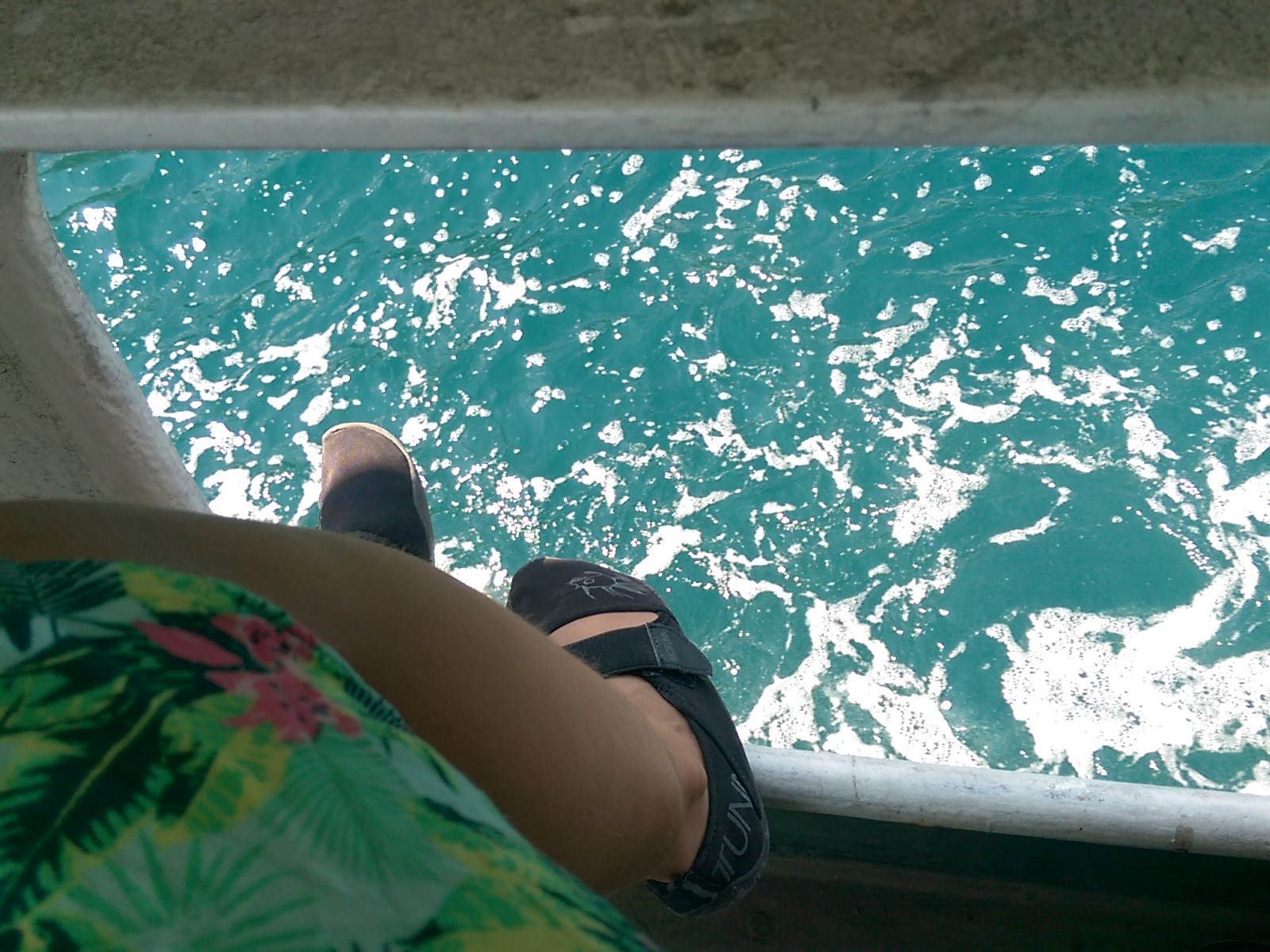 Looking down on bright blue foamy water, with the legs of a woman wearing a green skirt and black shoes