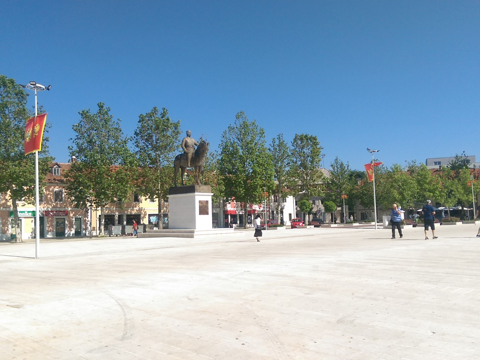 A paved concrete square with a statue of a man on a horse, some trees and people and blue sky