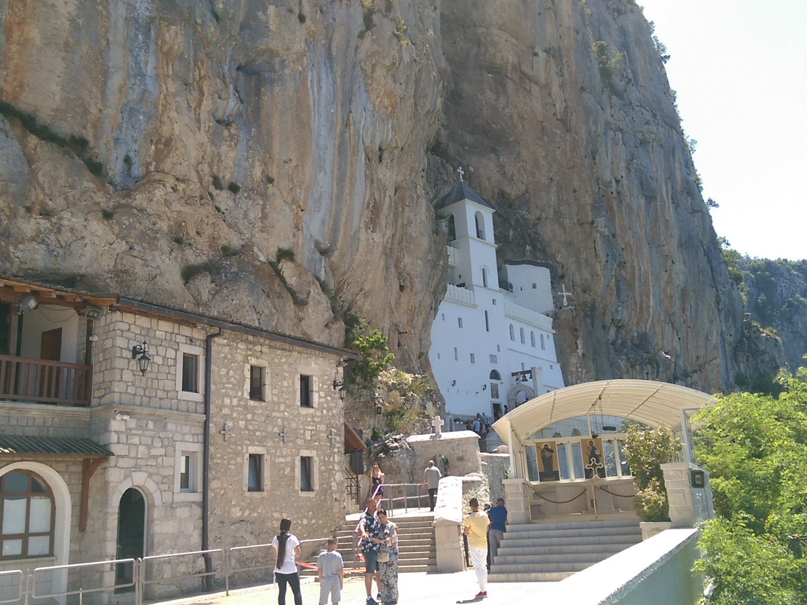 A vertical cliff face with buildings embedded in the side, and a courtyard with some tourists