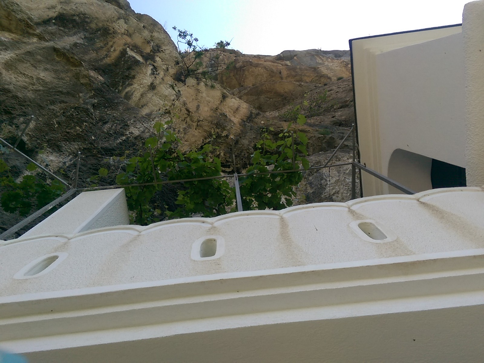 View from below of a white building and cliff rocks directly above