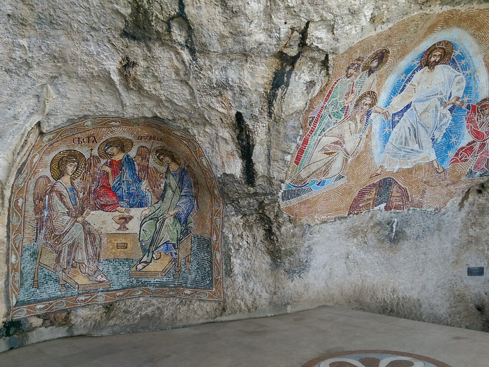 Raw rugged rock face with colourful but faded mosaics of religious figures