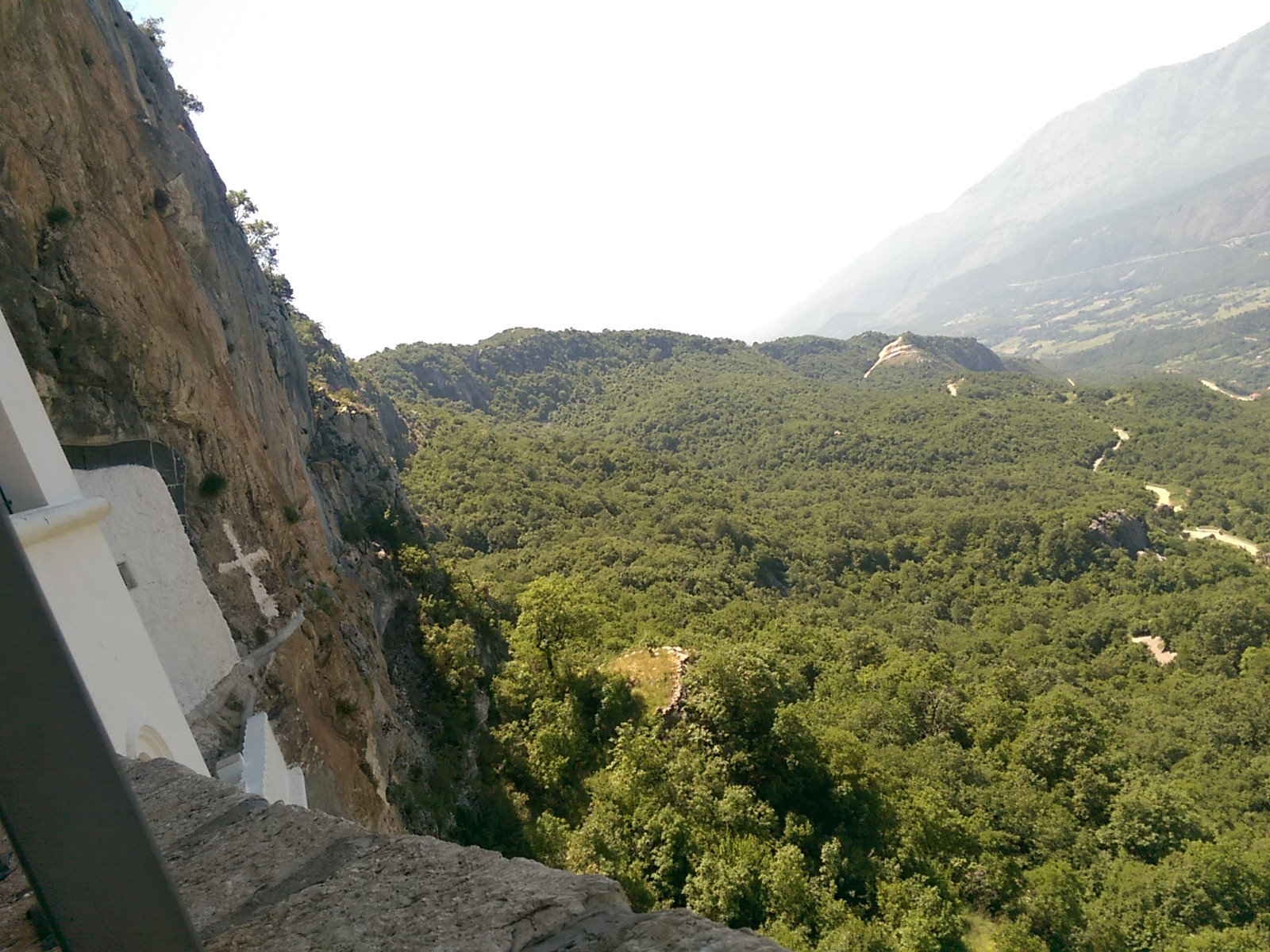Vertical cliff to the left and a view across a tree filled valley
