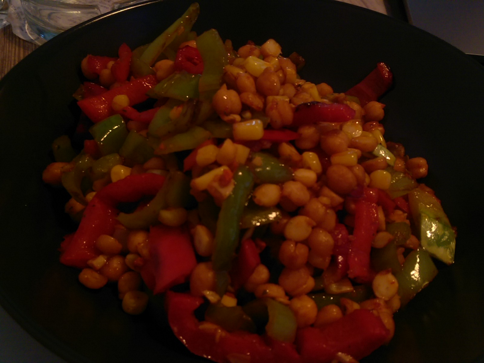 A bowl full of colourful peppers, corn and chickpeas