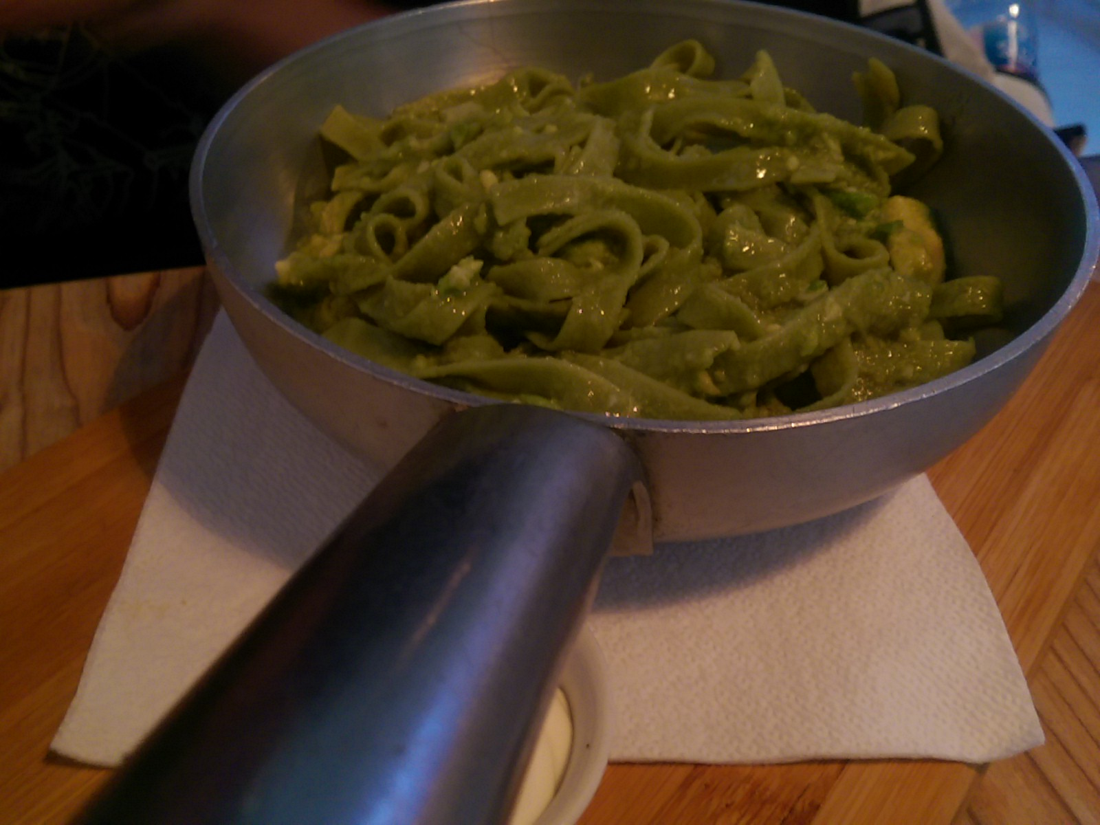 A metal pan with green strands of thick pasta