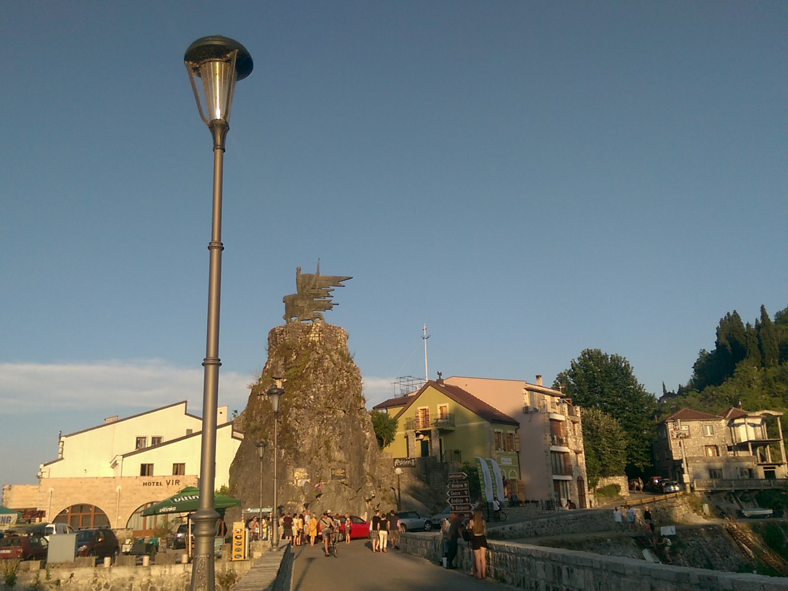 A small town with an abstract statue on a rock in the middle