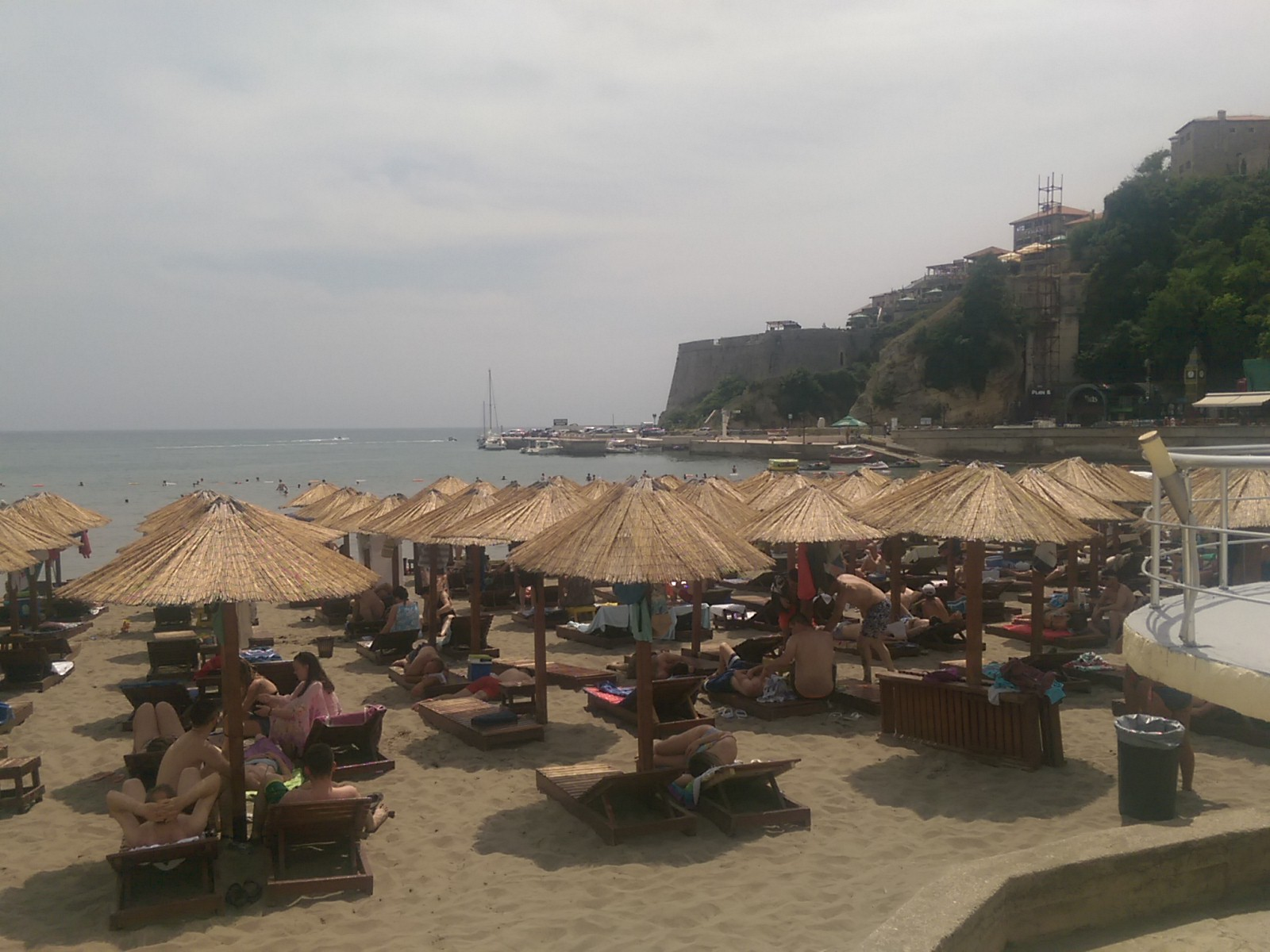 A beach overed in deckchairs and sun umbrellas, with the sea and an old town on a hill in the background