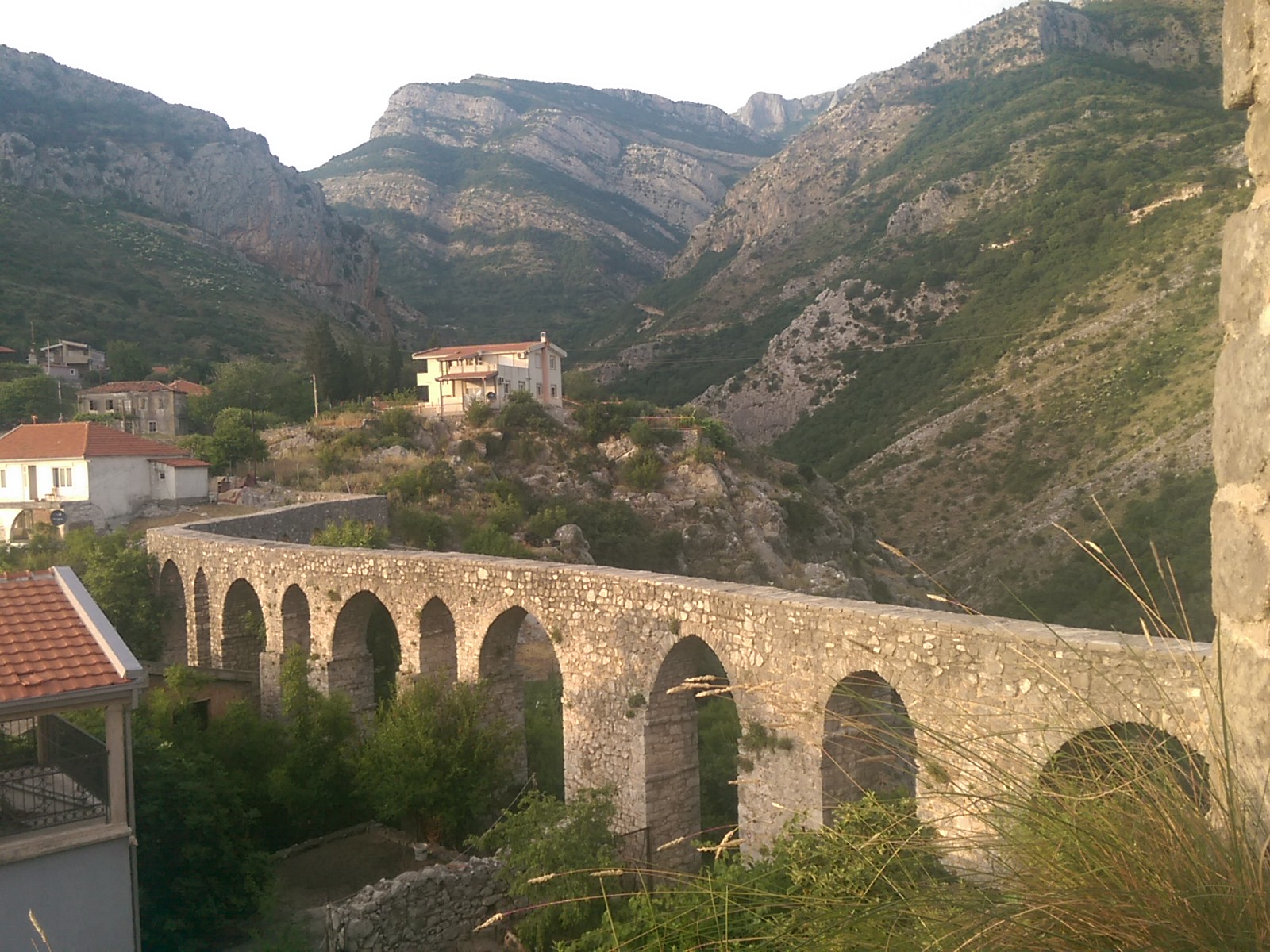 An aquaduct cuvers into the distance, between houses, backed by mountains with angular lines