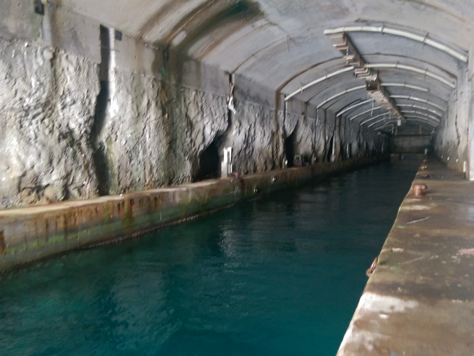 A long narrow whitewashed tunnel heading into the distance with walkways down each side and water in the middle