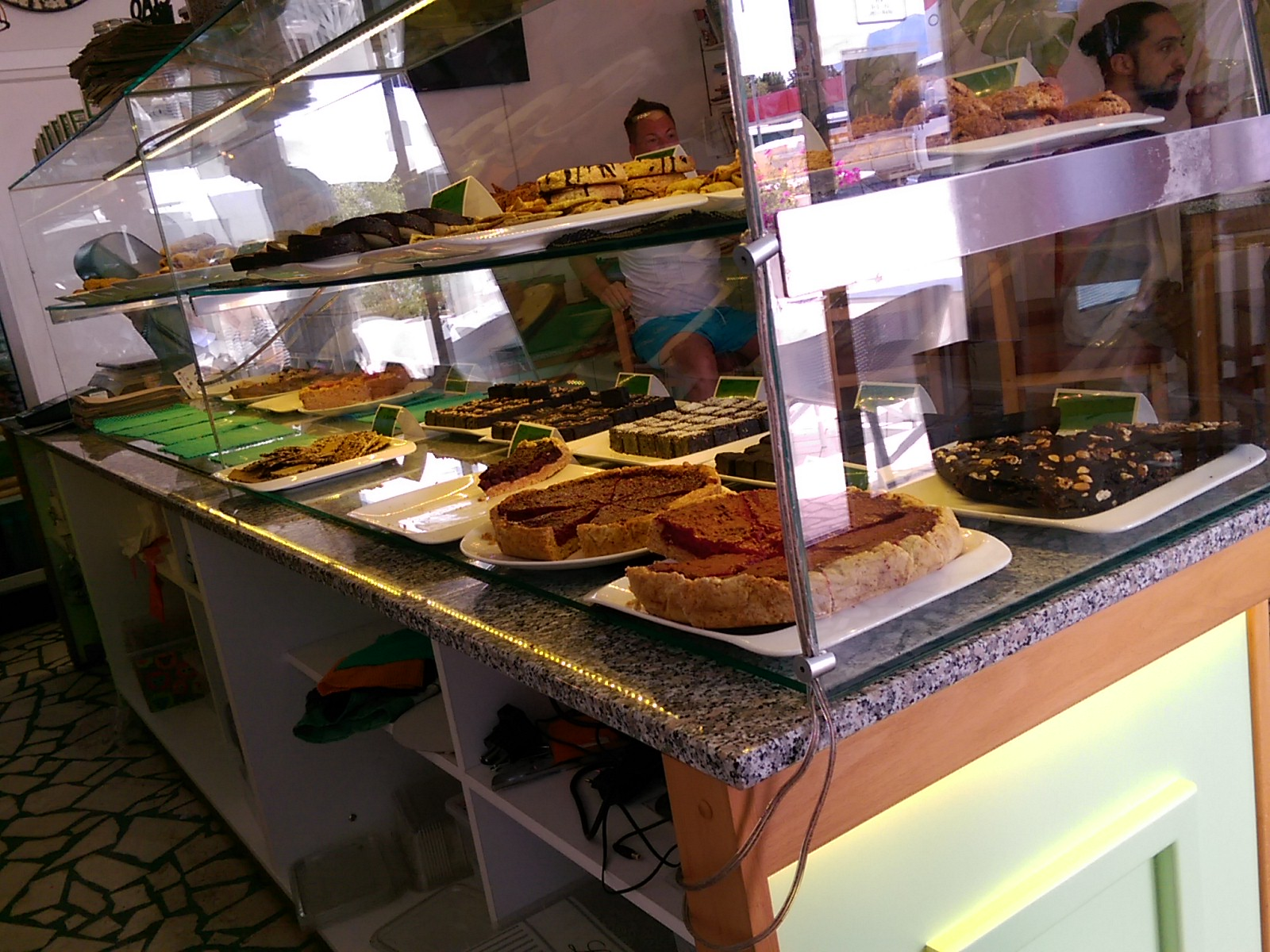 A glass counter full of cakes and pie