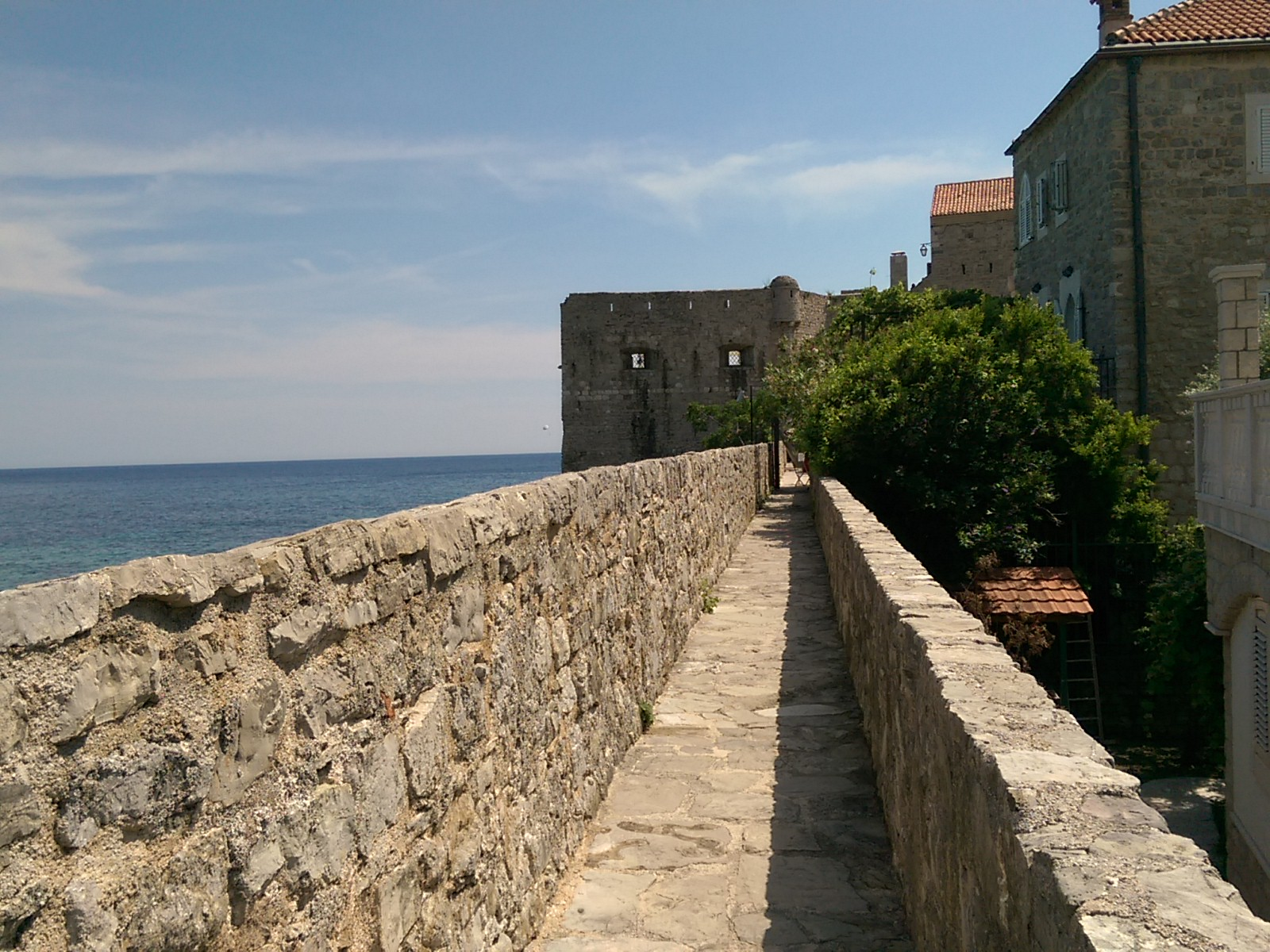 Narrow city wall walkway stretches into the distance, with sea to the left and stone houses to the right