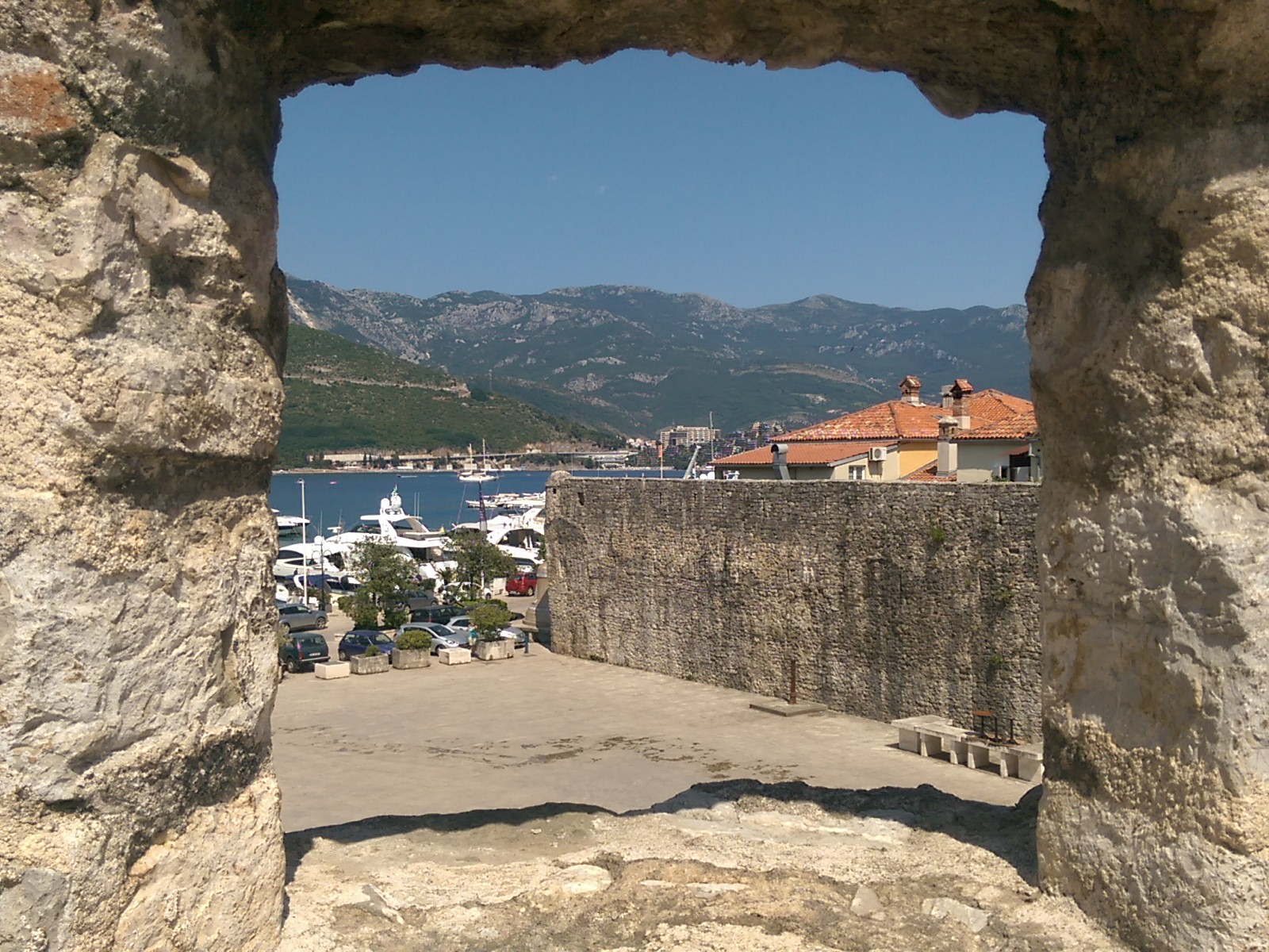 A stone square window with a view to sea, port, mountains