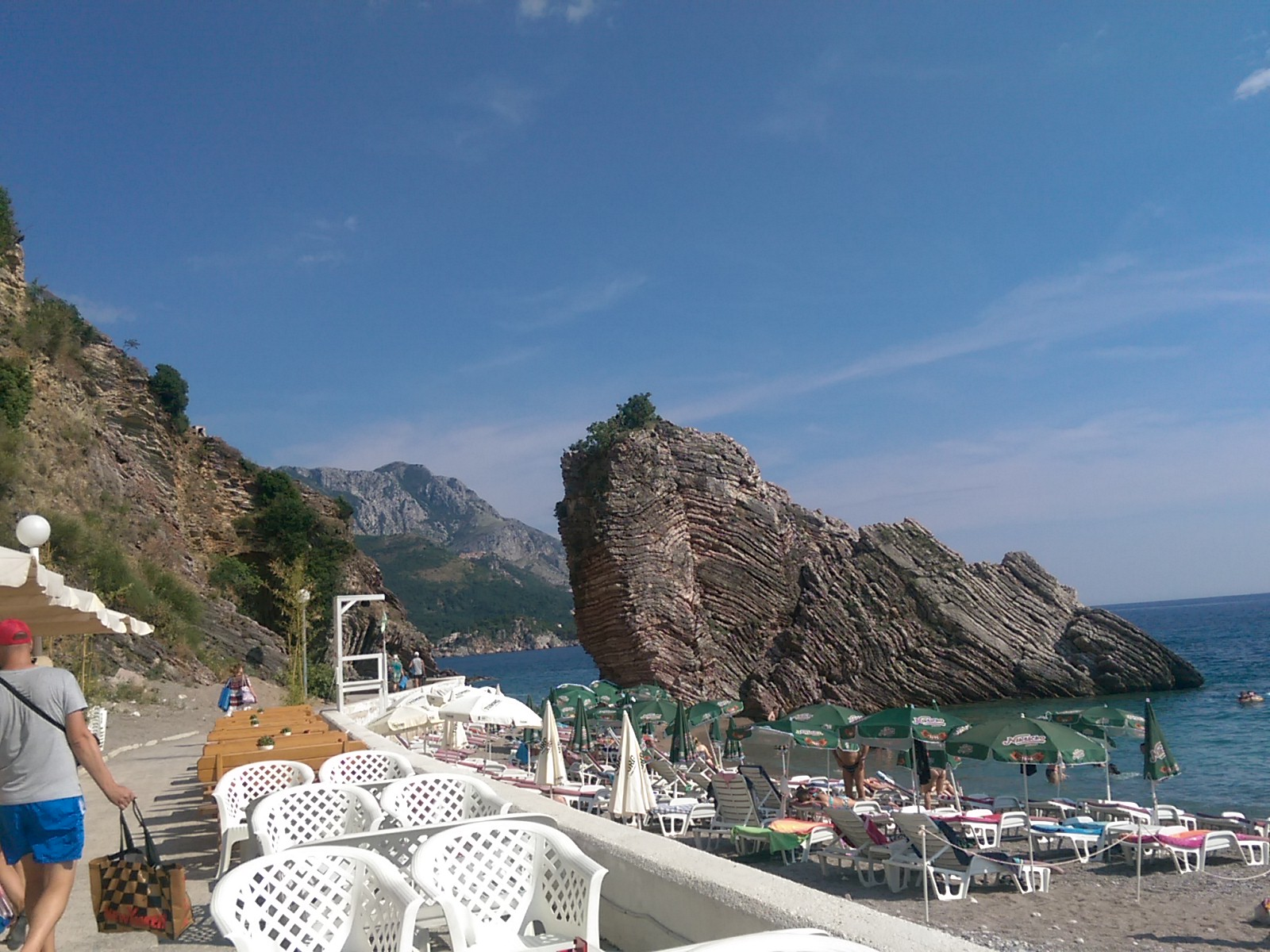 A stone beach covered in sunbeds and people, with people swimming in the sea around a rock shaped like a sinking ship