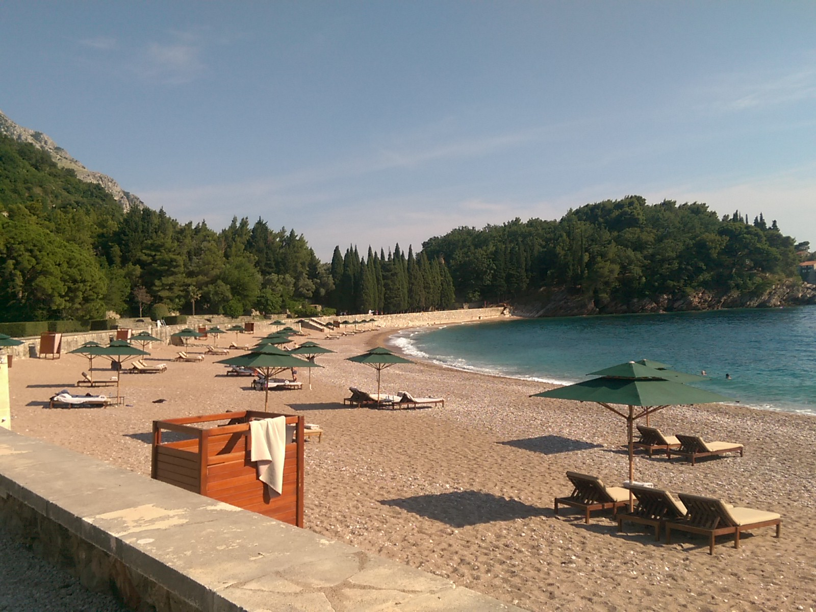 A clear sand beach curves to the left with empty sunbeds and blue sea, lined with trees