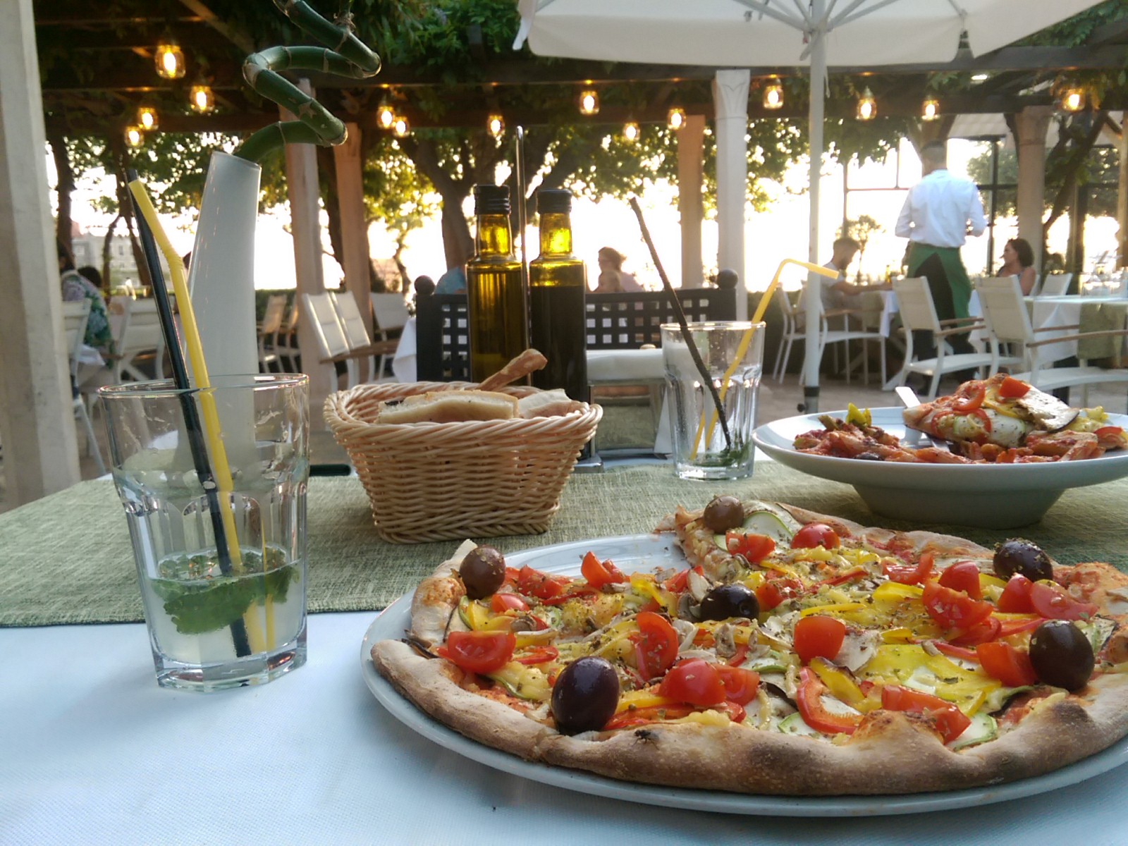 A pizza in the foreground by a mostly finished glass of mint lemonade, and a fancy restaurant with plants and lights in the background