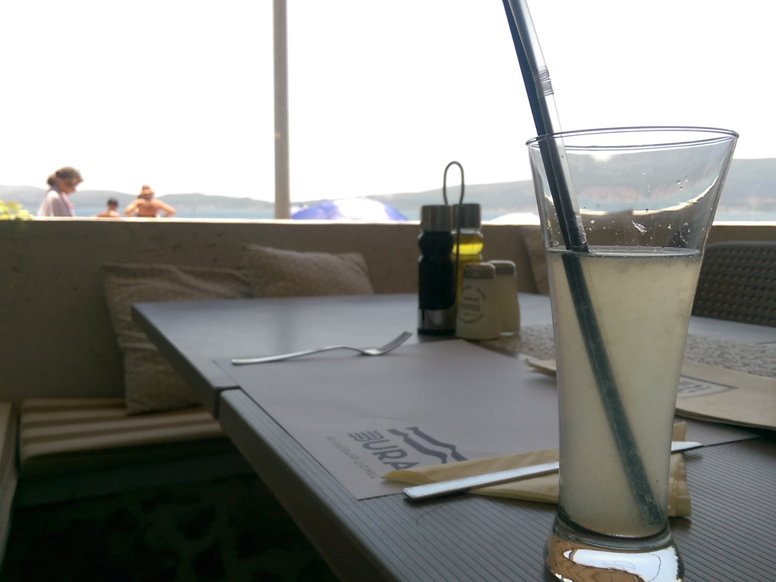 A tall glass of lemonade in the foreground on a table with cafe benches