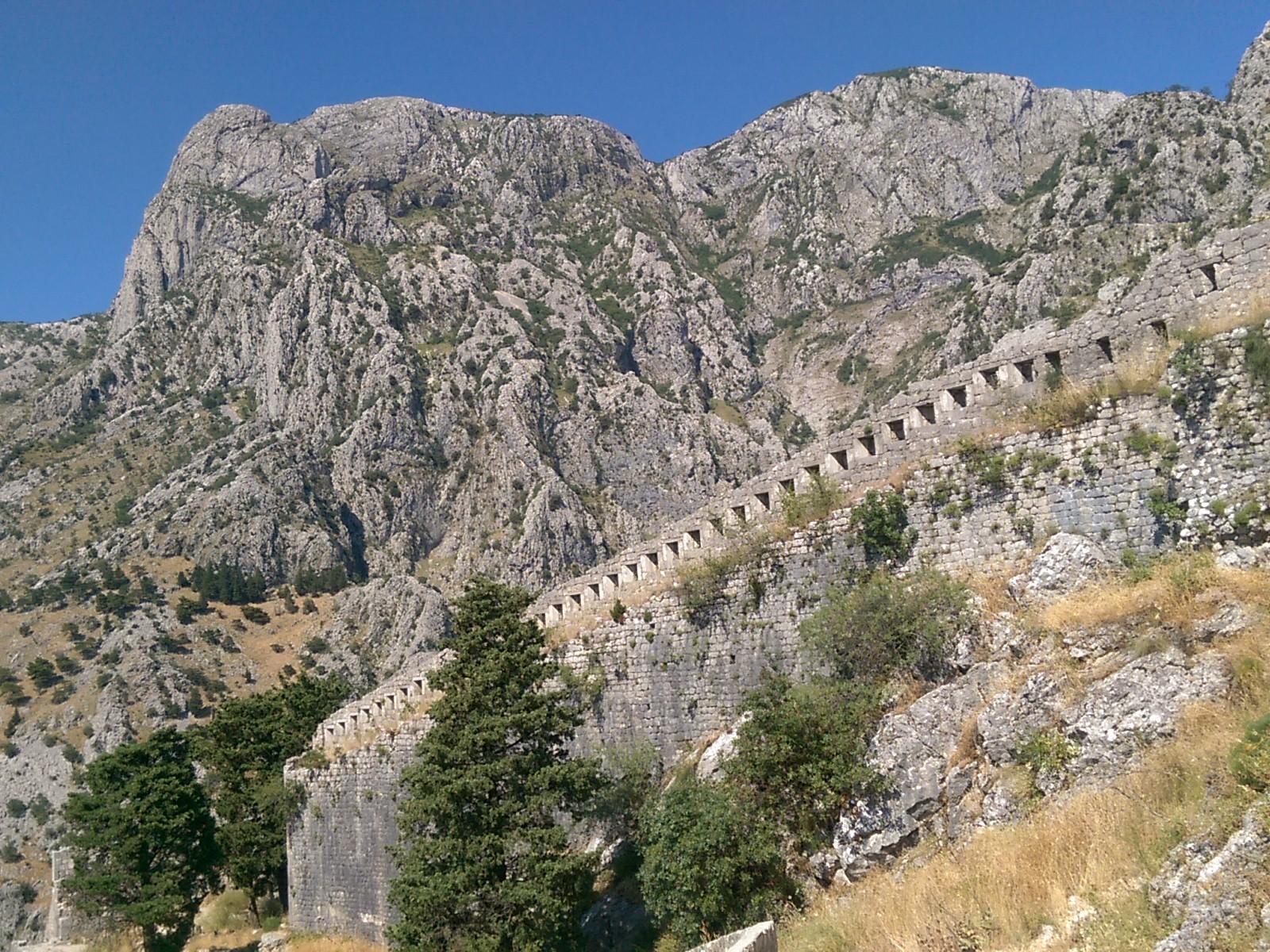 Stone city walls are almost disguised against rough rocky mountains under a clear blue skky