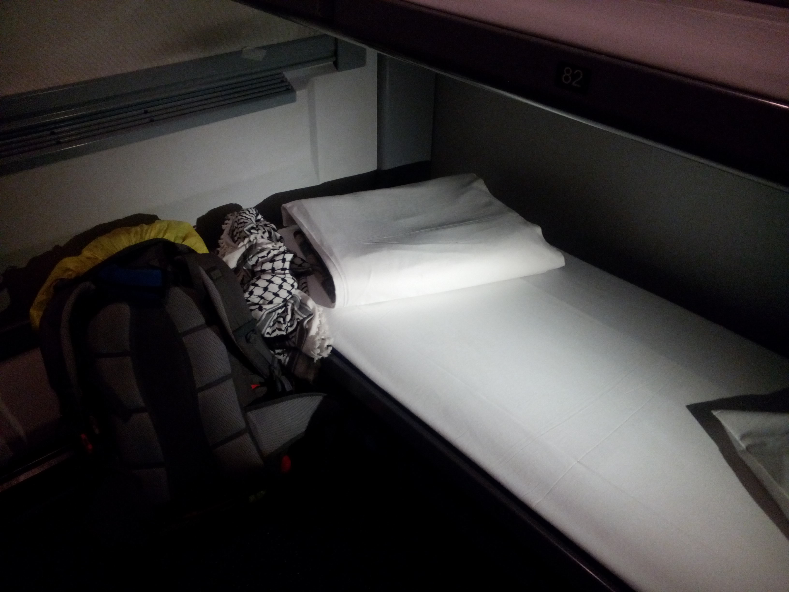A narrow bottom bunk in a train cabin with a backpack next to it