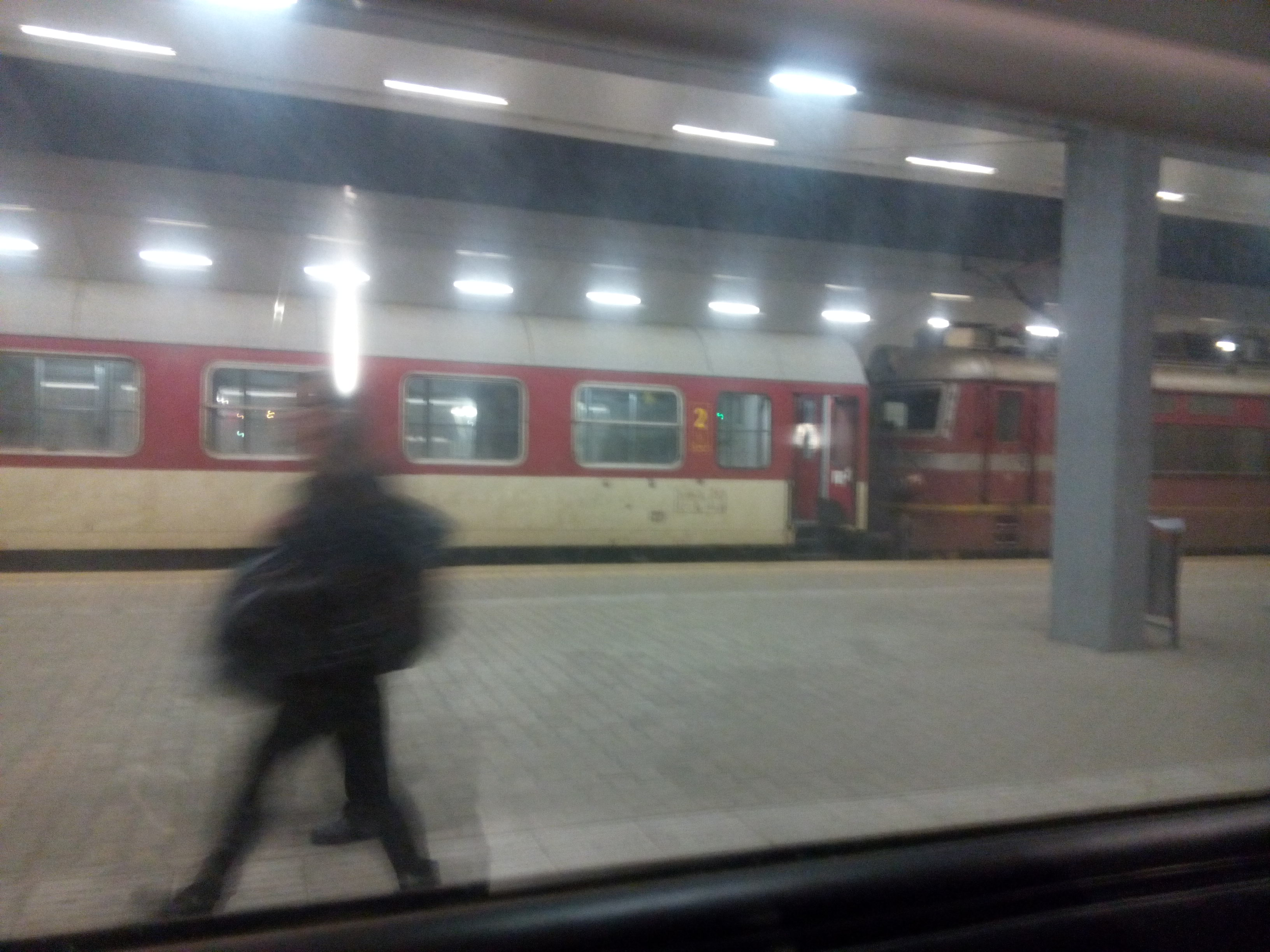 View from a train window onto a platform, with a blurry person walking by and a red and yellow train on the opposite track