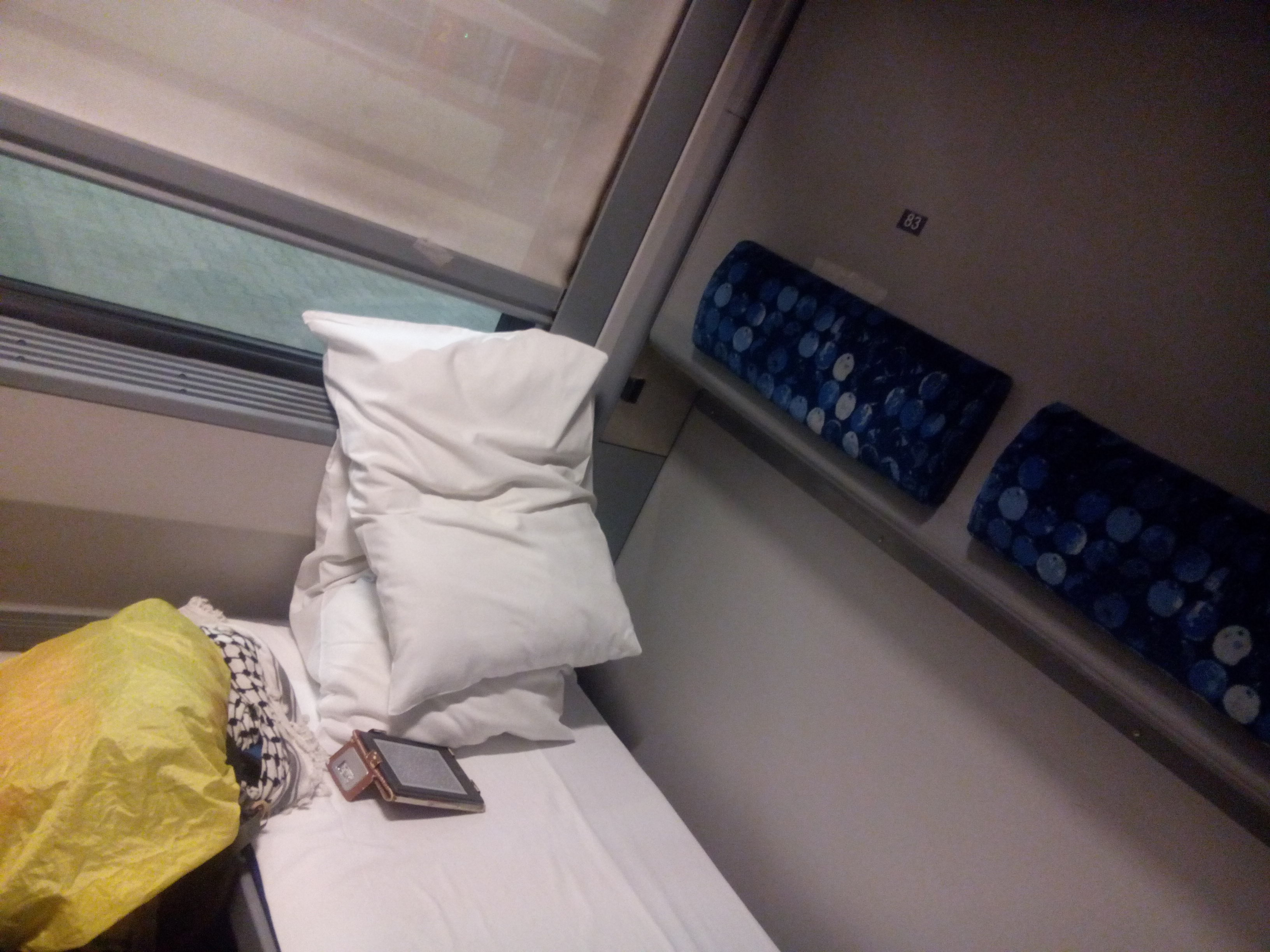 Two pillows on a small bed in a train cabin, with a kindle