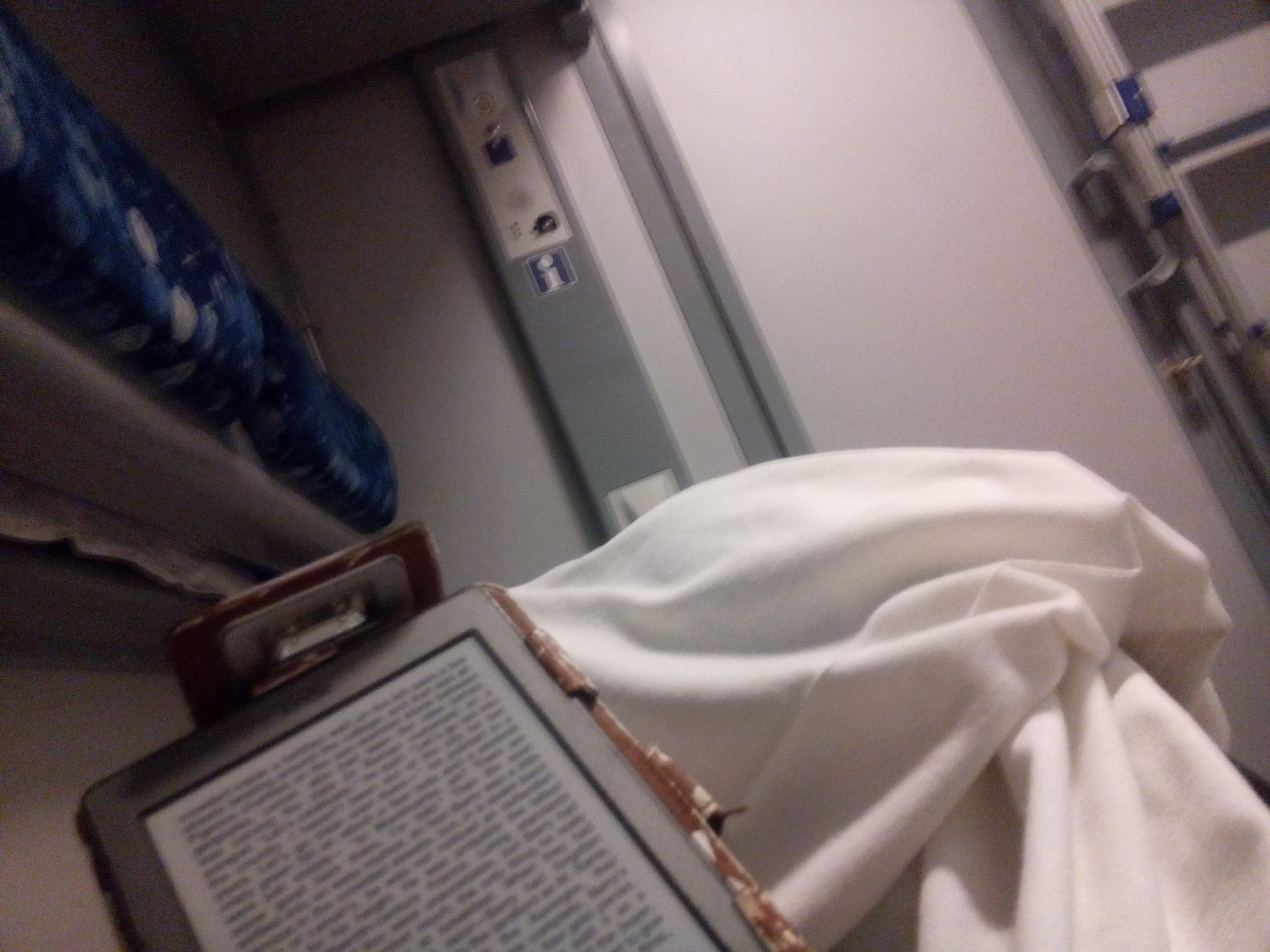 A kindle held from the perspective of someone lying in bed reading