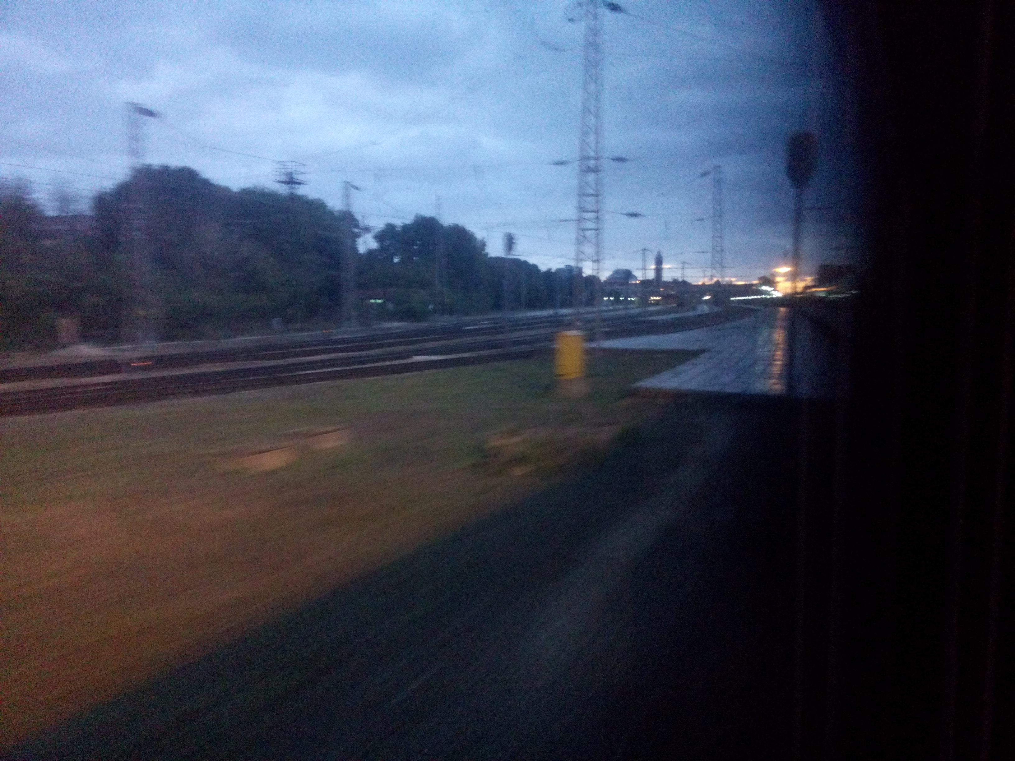 View from a train window onto tracks, with pale sunrise in the distance