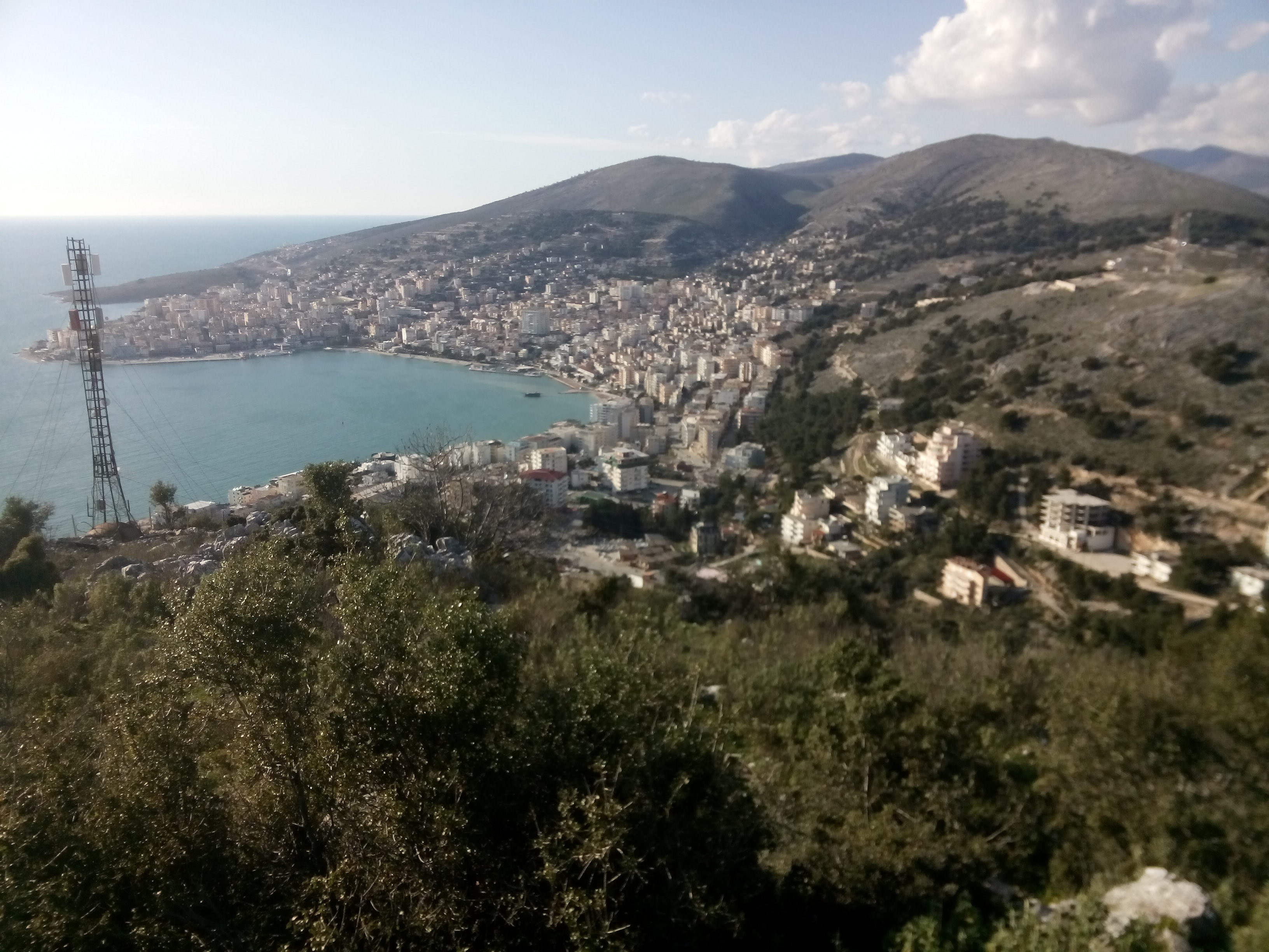 View from a hill over a small city lining a bay, backed by mountains