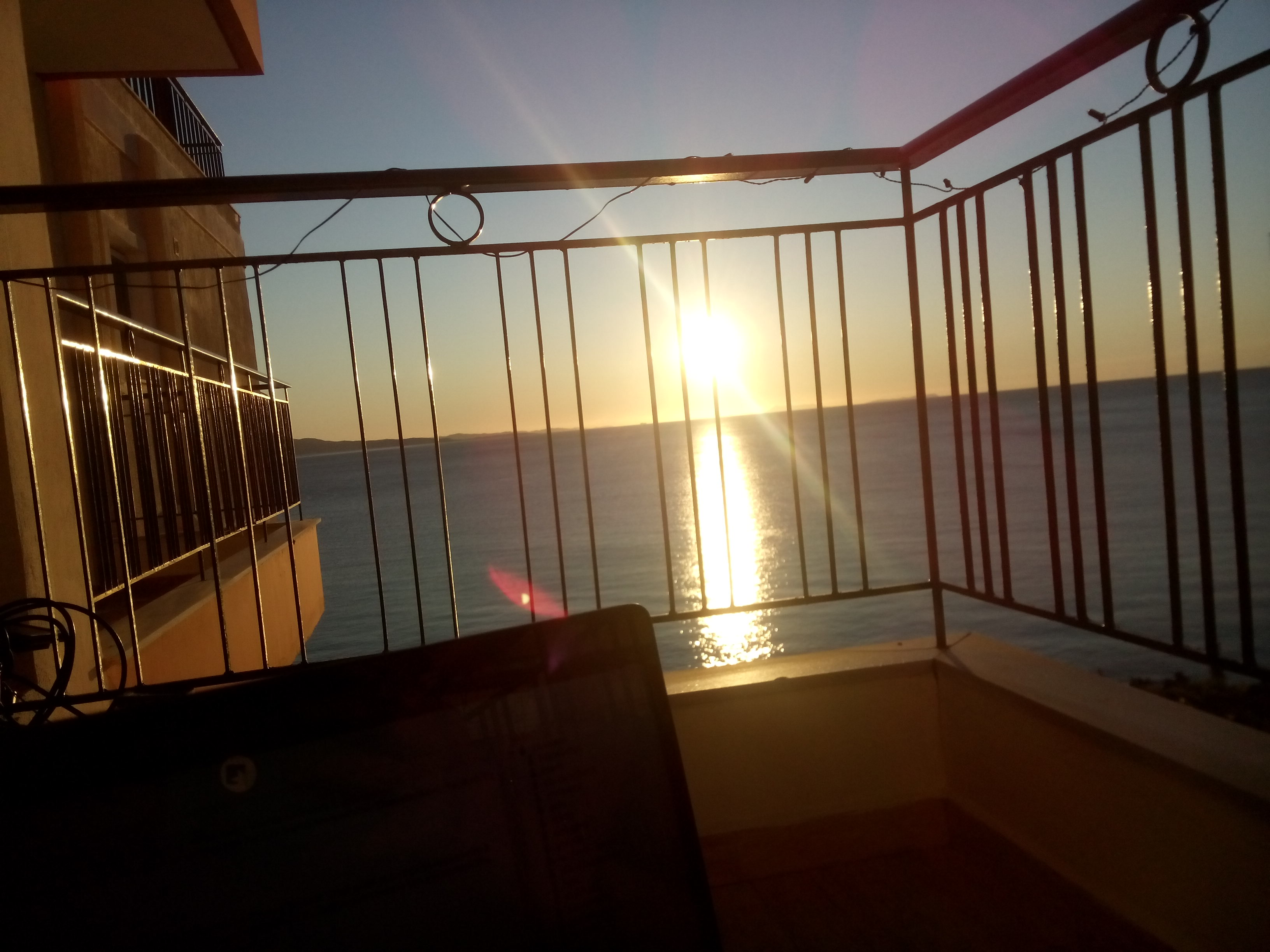 A sunset over the sea from a balcony