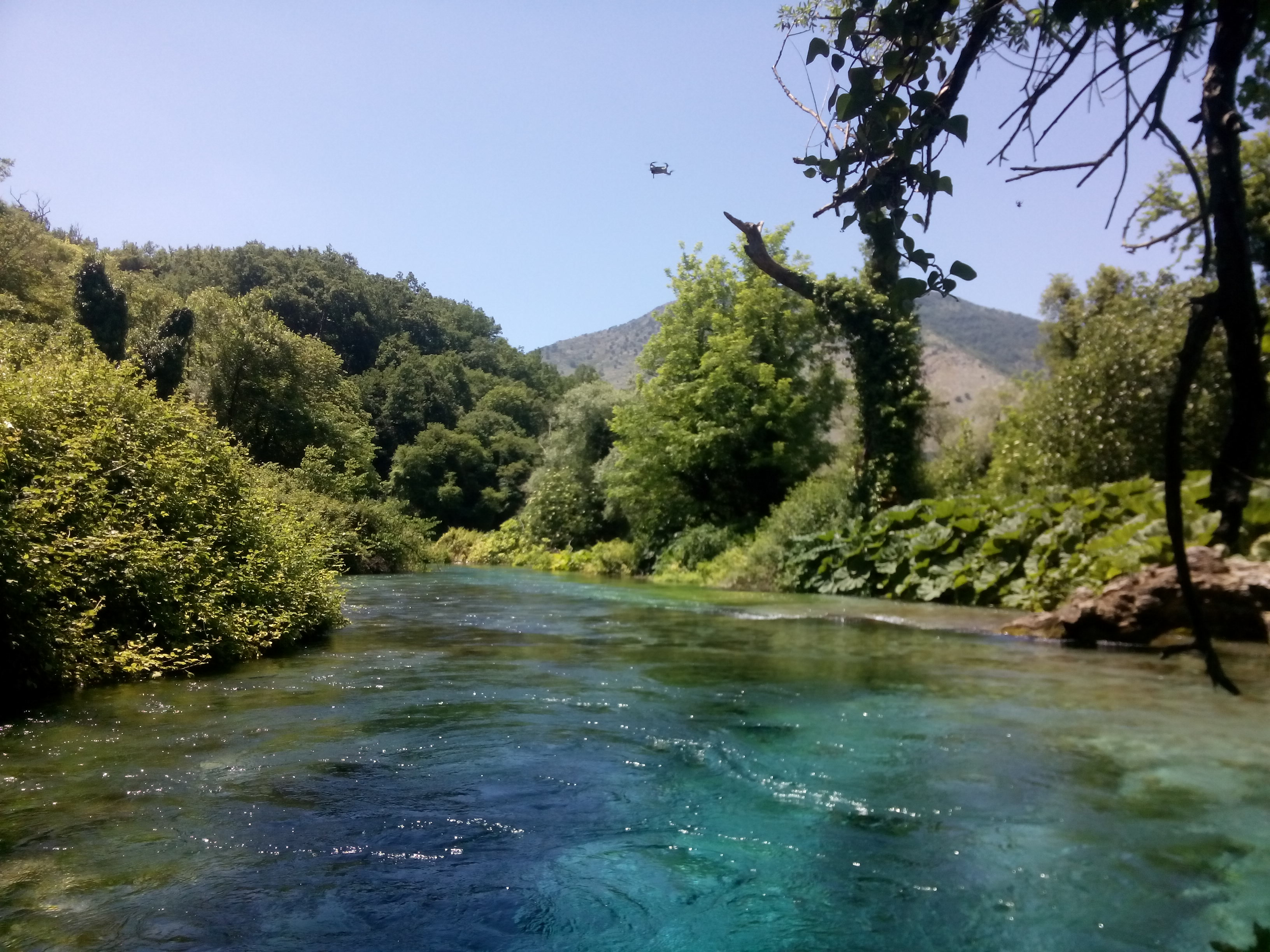 A view across a bright blue bubbling spring with trees around and mountains in the background