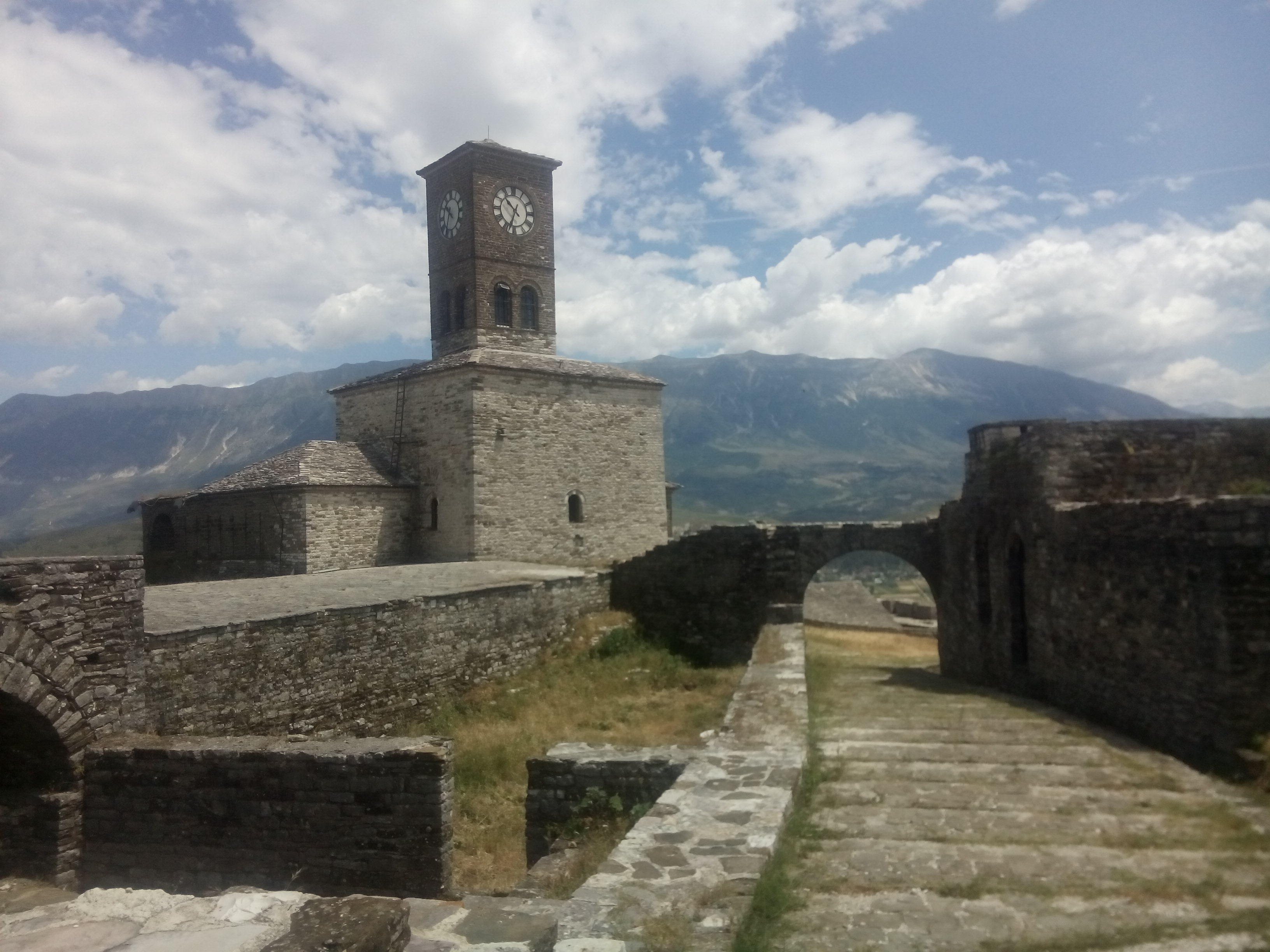 Stone walls and clock tower of Gjirokaster castle with mountains in the background