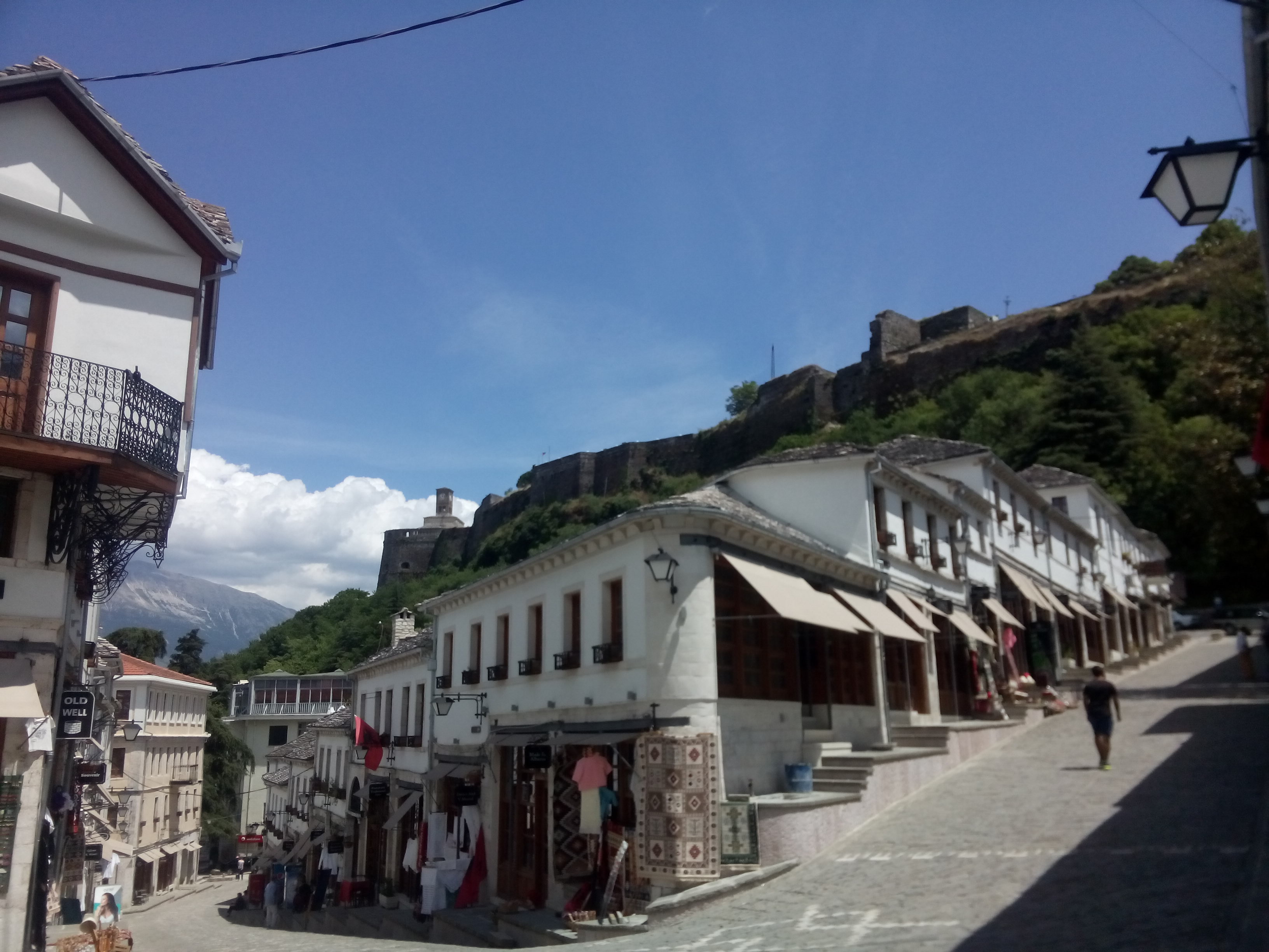 Sloping paved streets with white walls, open shop fronts, mountains in the background and a blue sky