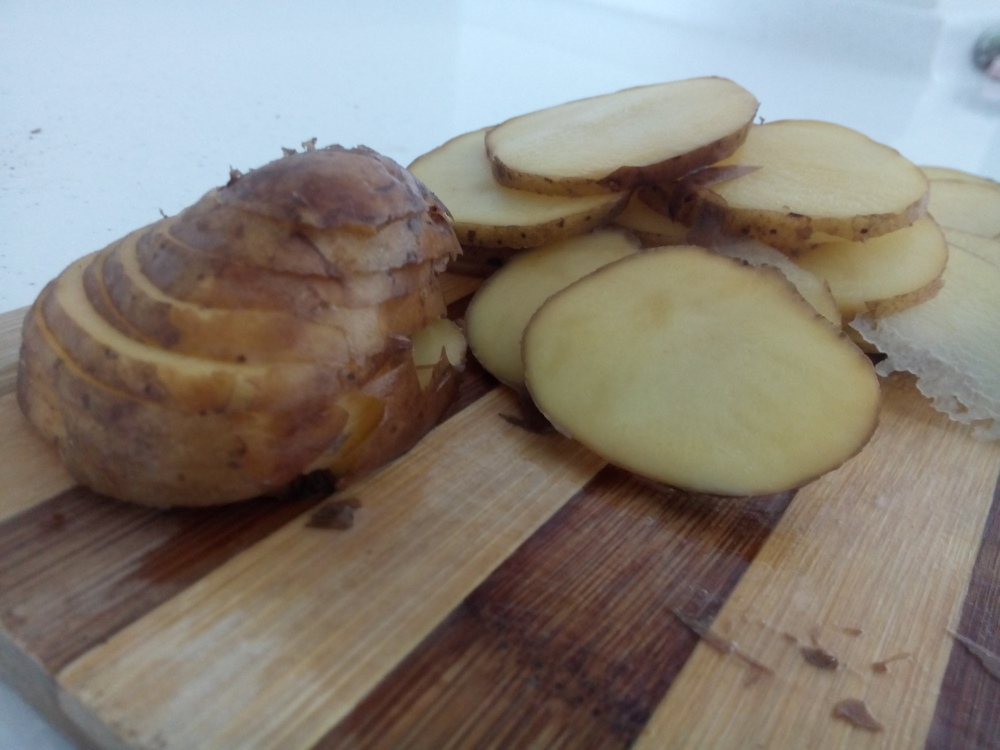 Sliced potato on a wooden chopping board