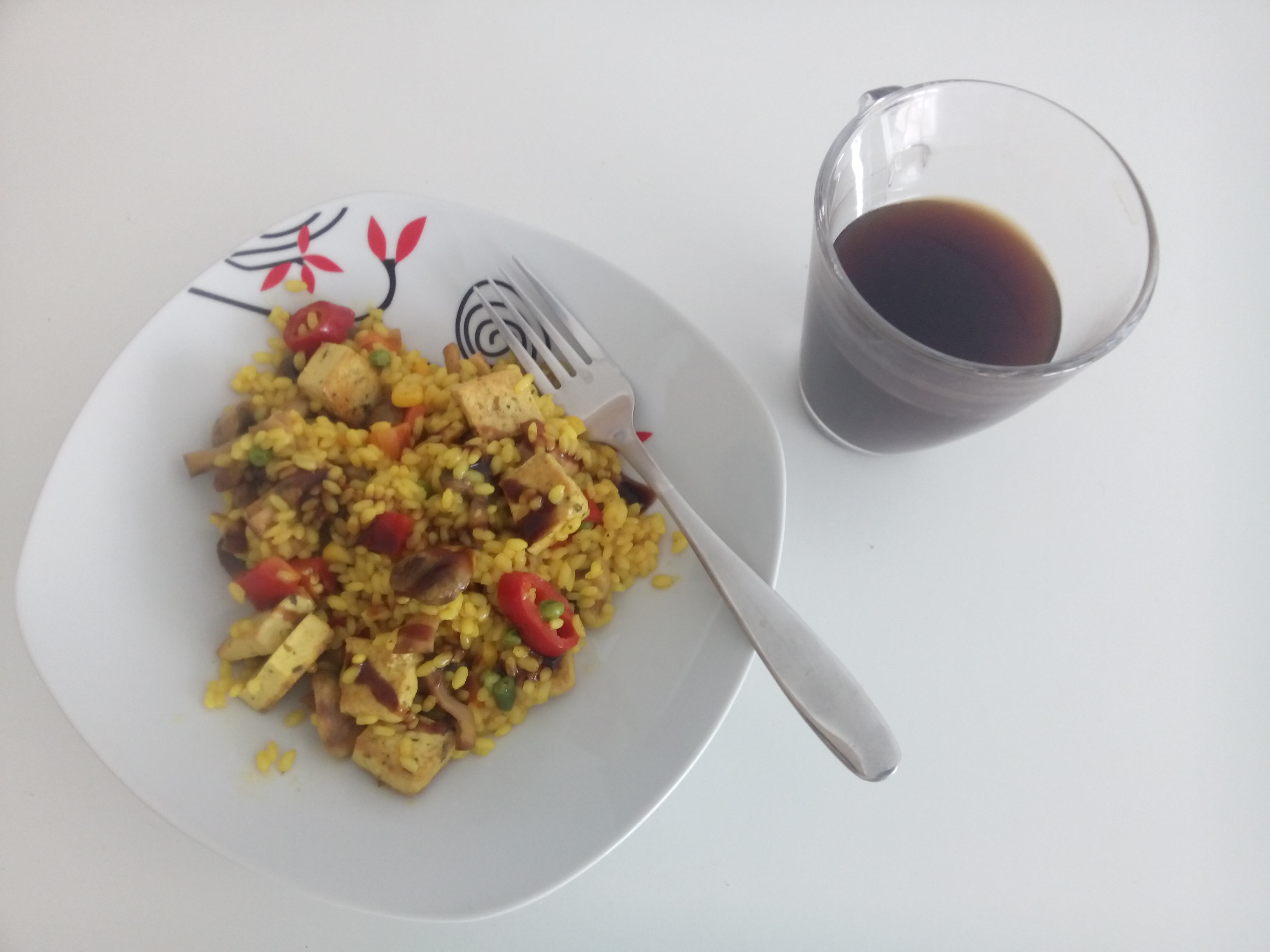 a bowl of yellow rice with colourful veggies on a white table beside a fork and glass mug of black coffee