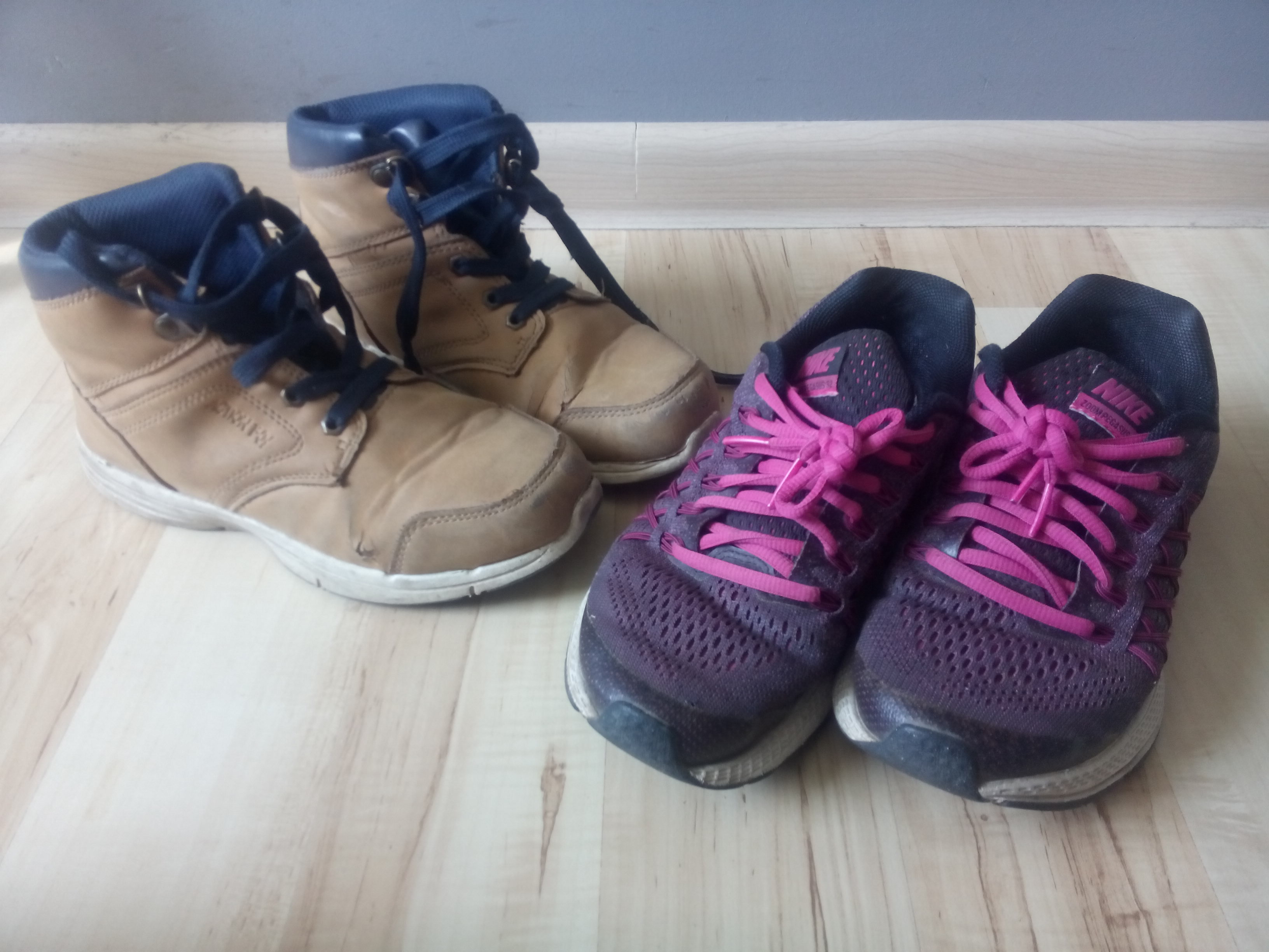 A pair of large tan and blue laceup boots beside a pair of pink and purple running shoes