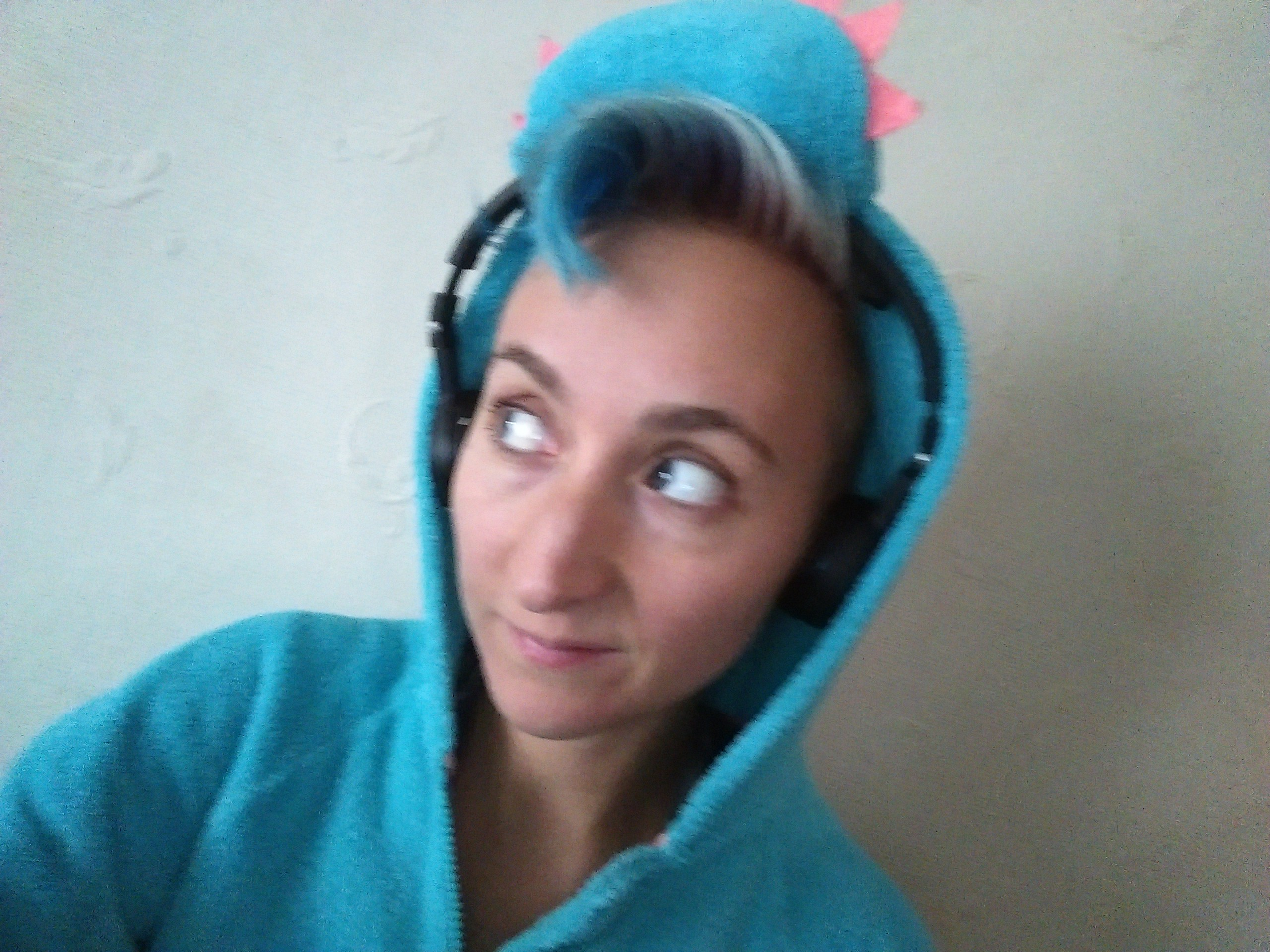 Person in blue dinosaur hood with wireless headphones and blue hair
