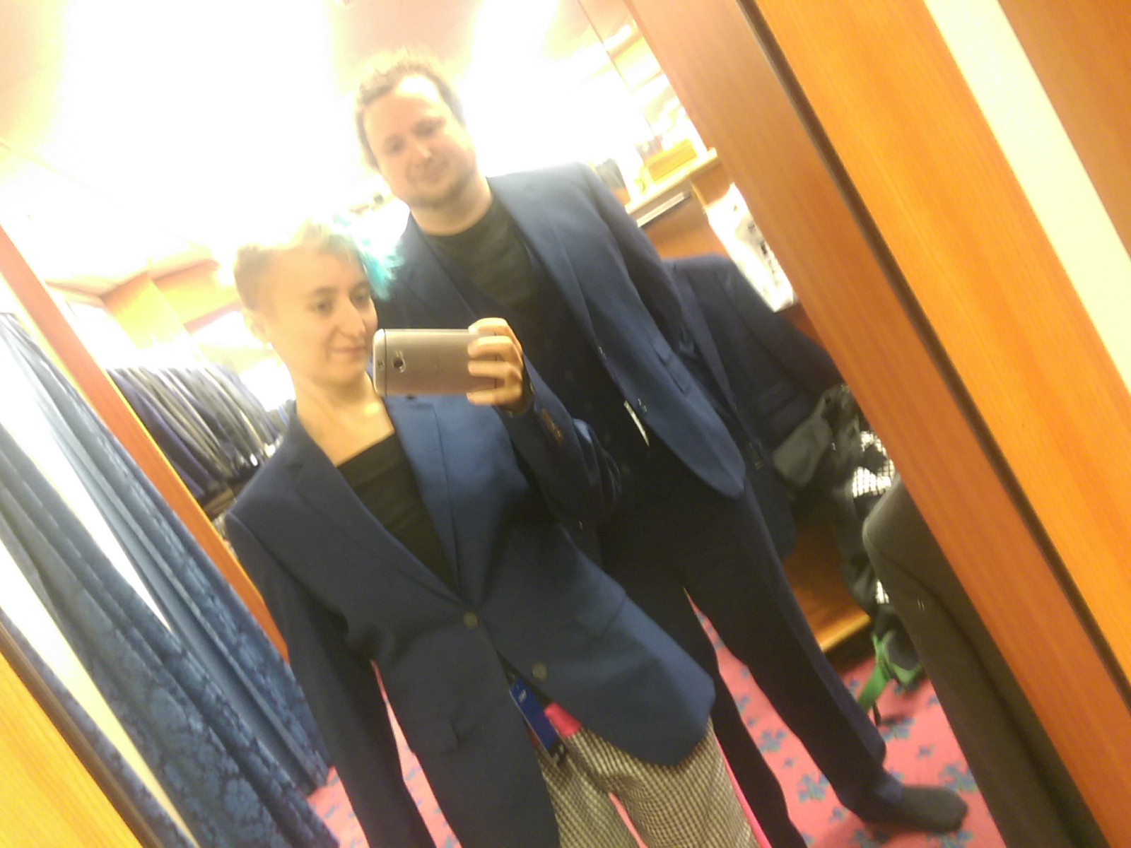 A selfie of two different sized humans in a mirror, wearing navy blue jackets in a suit shop