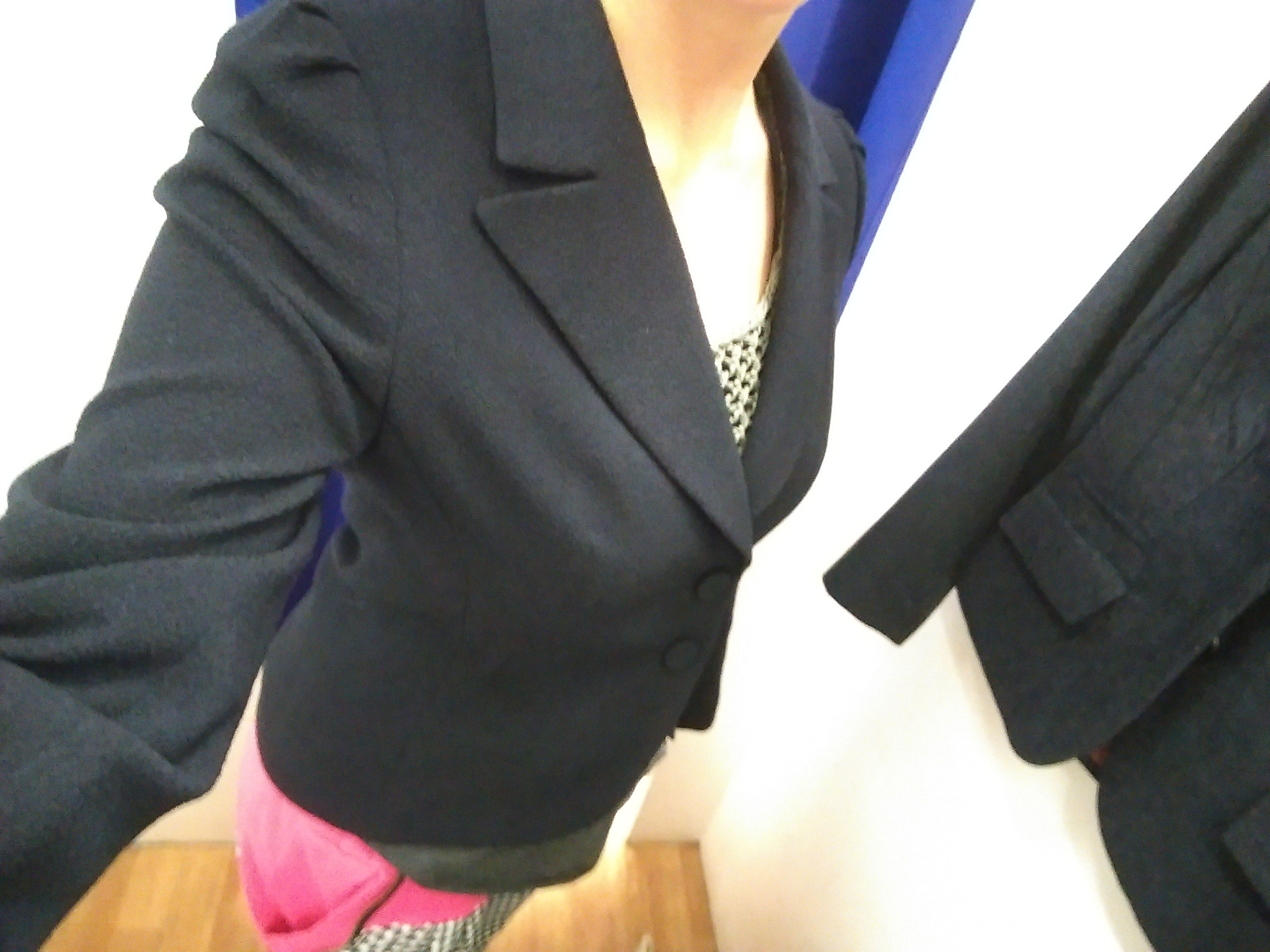 A selfie of a torso wearing a navy suit jacket and pink trousers in a shop changing room