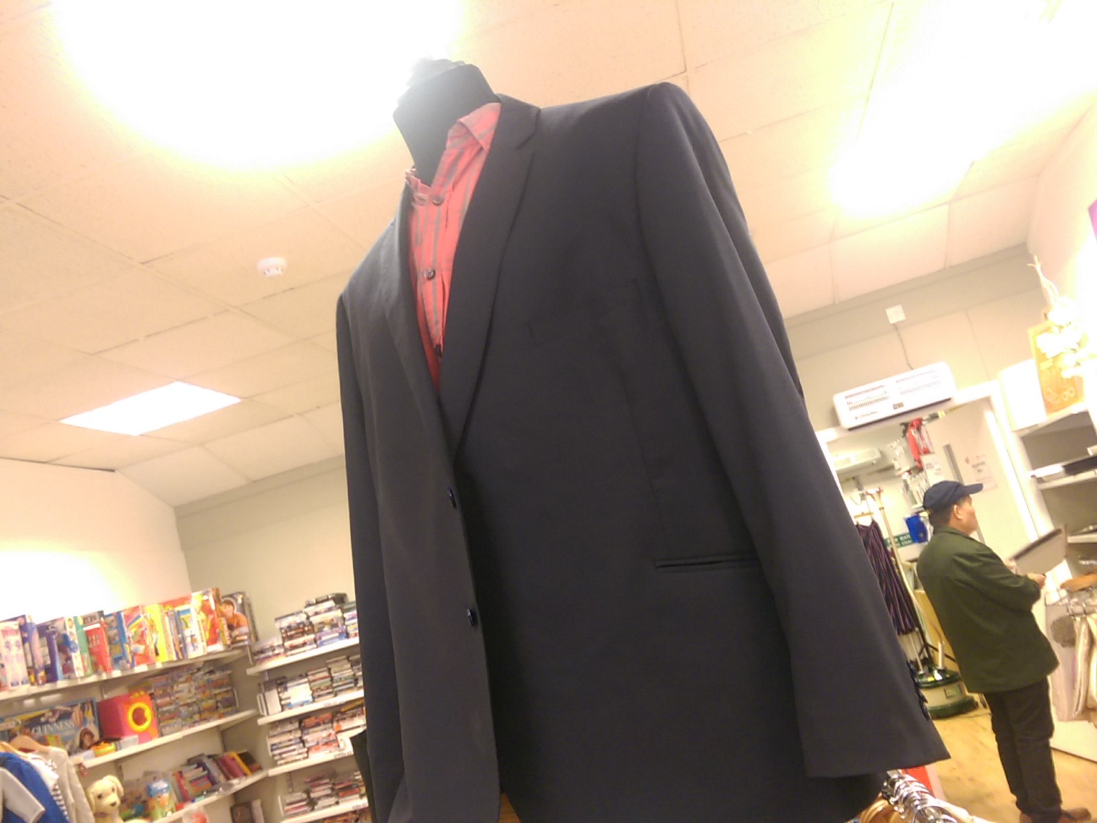 A navy suit jacket on a tailor's dummy with a pink shirt