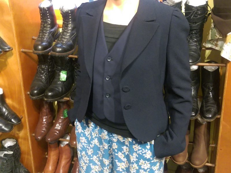 A torso wearing a navy blazer and wasitcoat, and flowery blue trousers, in front of a rack of shoes