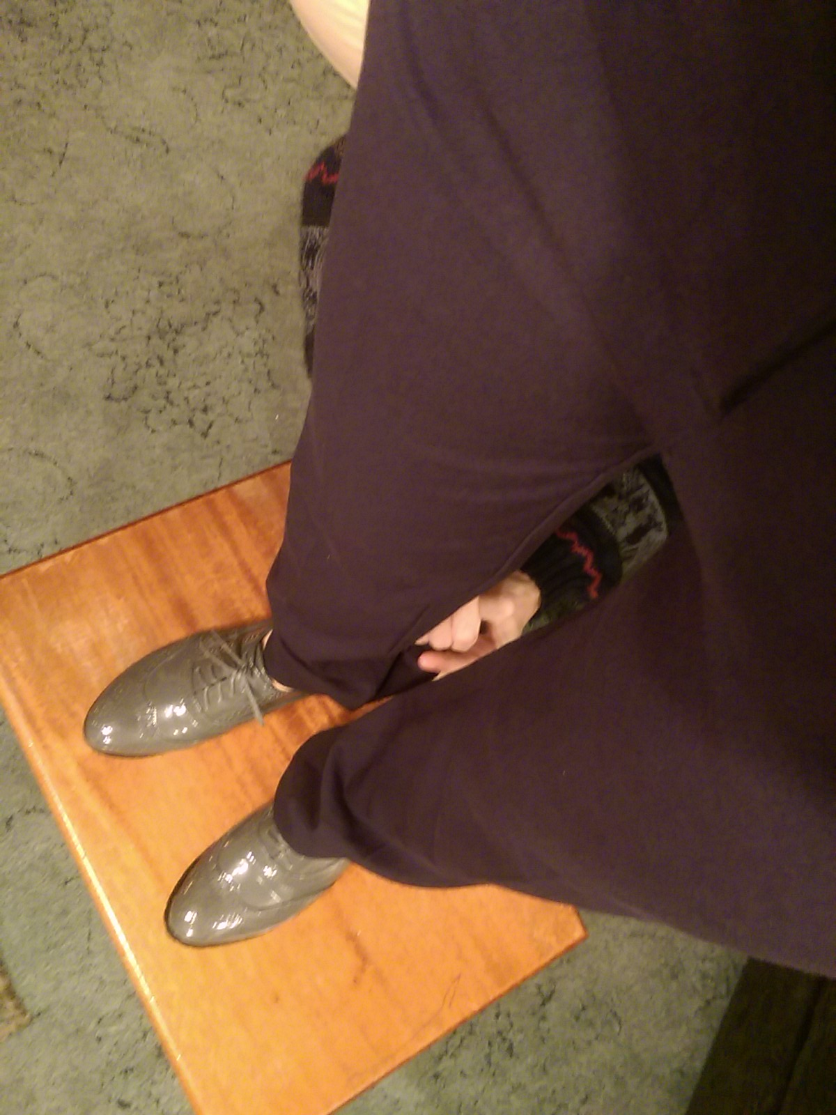 View from above of someone's legs with navy trousers, being adjusted