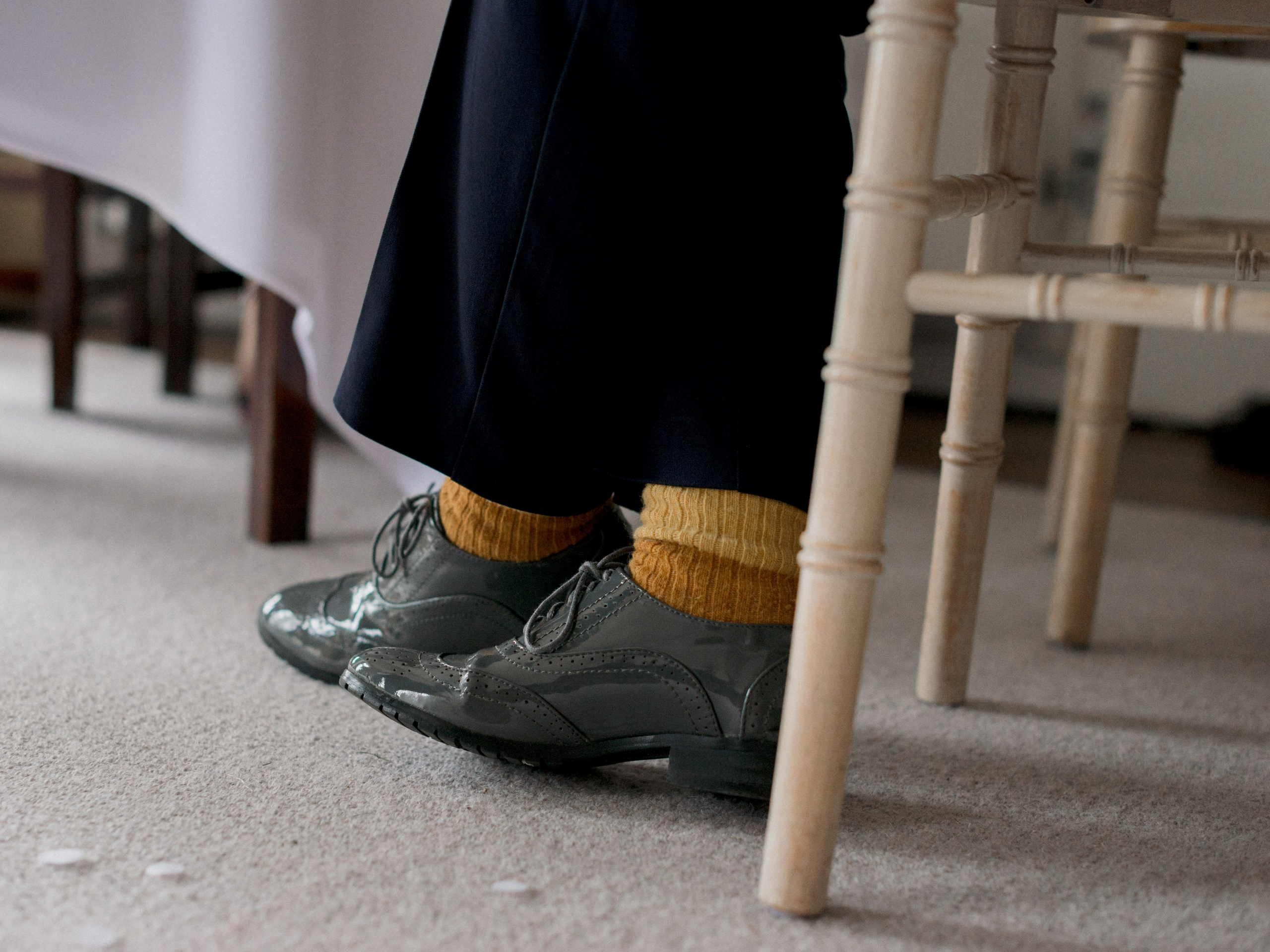 Feet of a person sitting on a white chair, crossed over, with grey brogue shoes and mustard socks