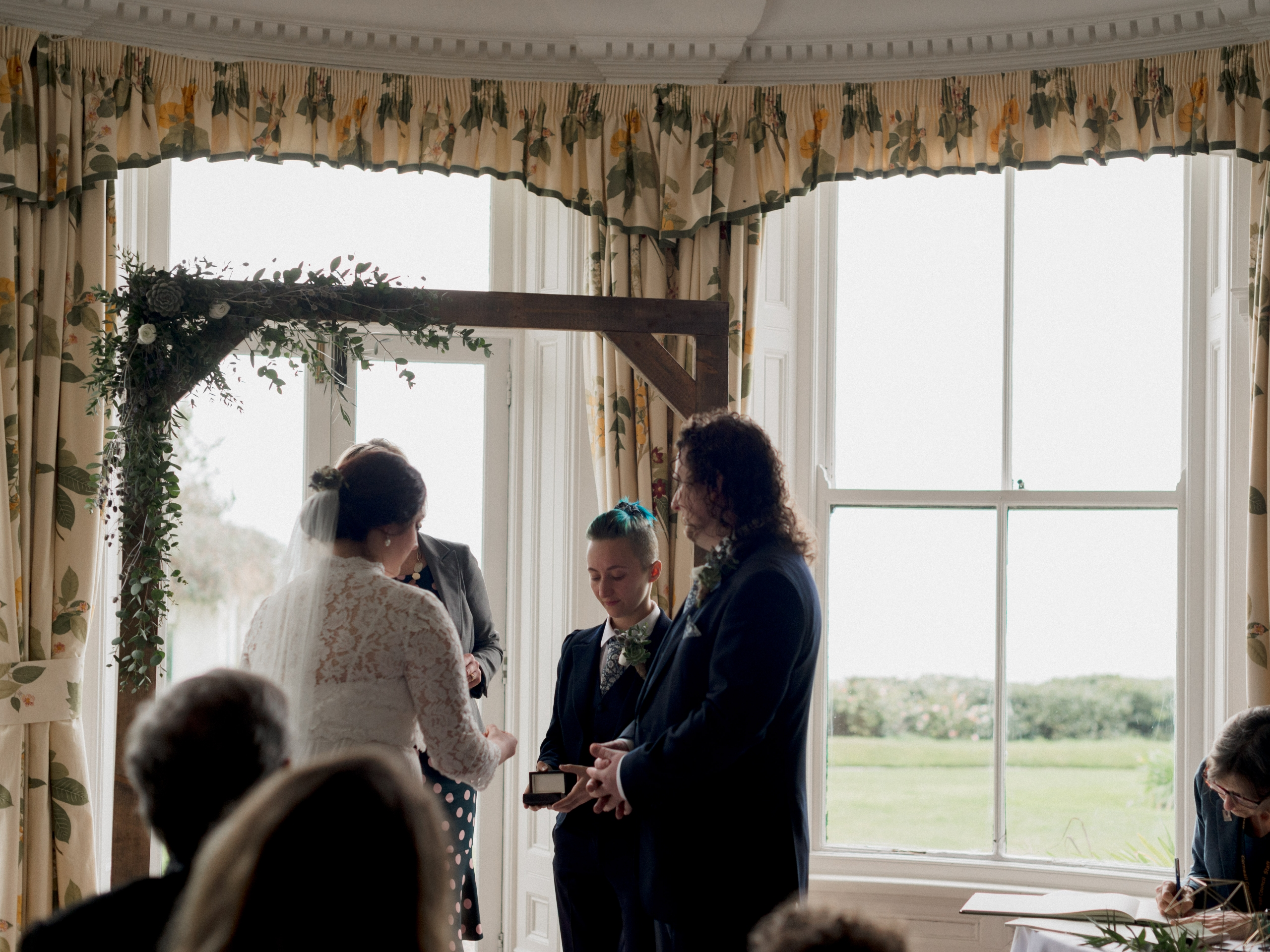 A bride and groom stand under a leafy wooding wedding arch, with the Best Man offering rings from a box, in front of a large window with a view of the sea