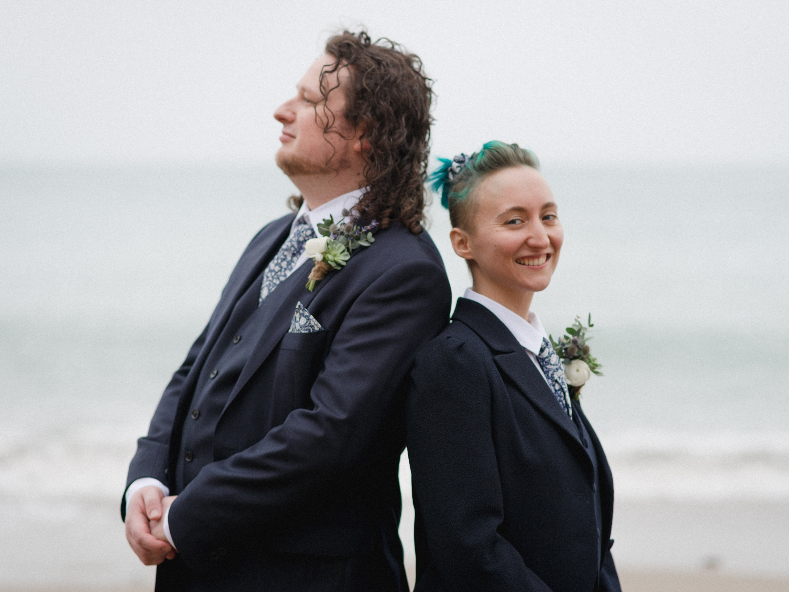 Two people in suits stand back to back with the sea behind