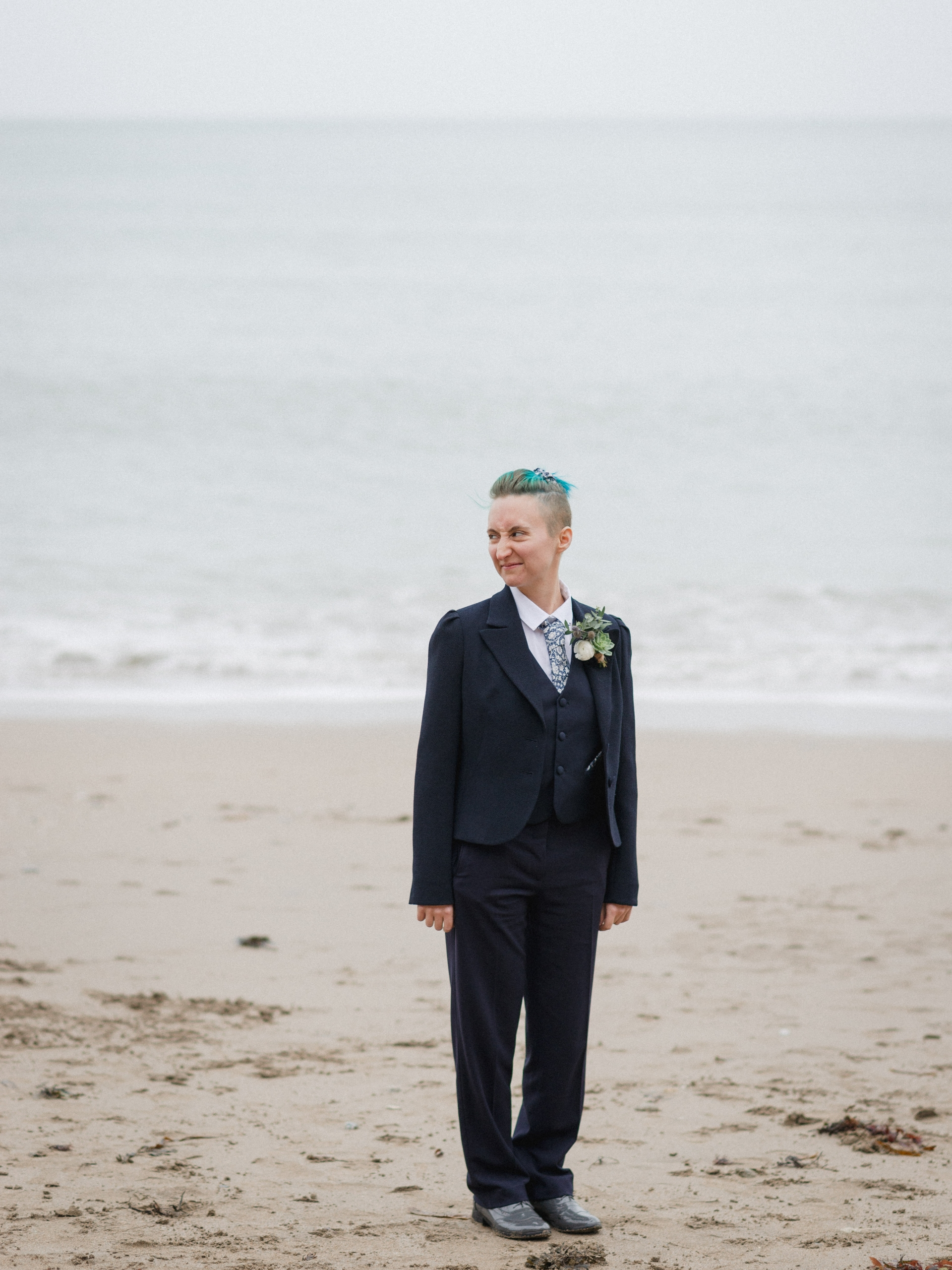 A person in a navy suit stands on sand in front of the sea, looking over to the left
