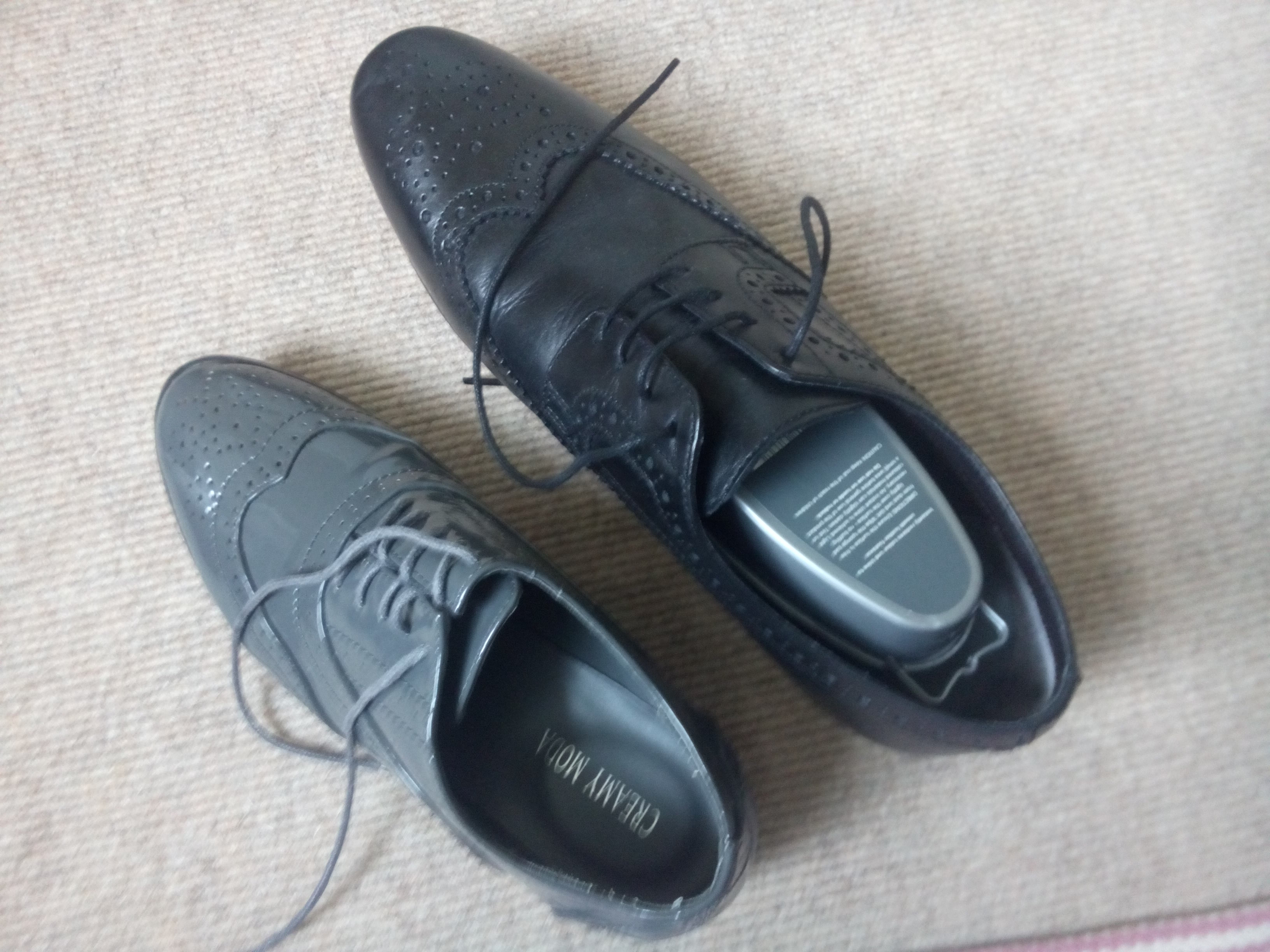 A small grey brogue shoe beside a large black brogue shoe
