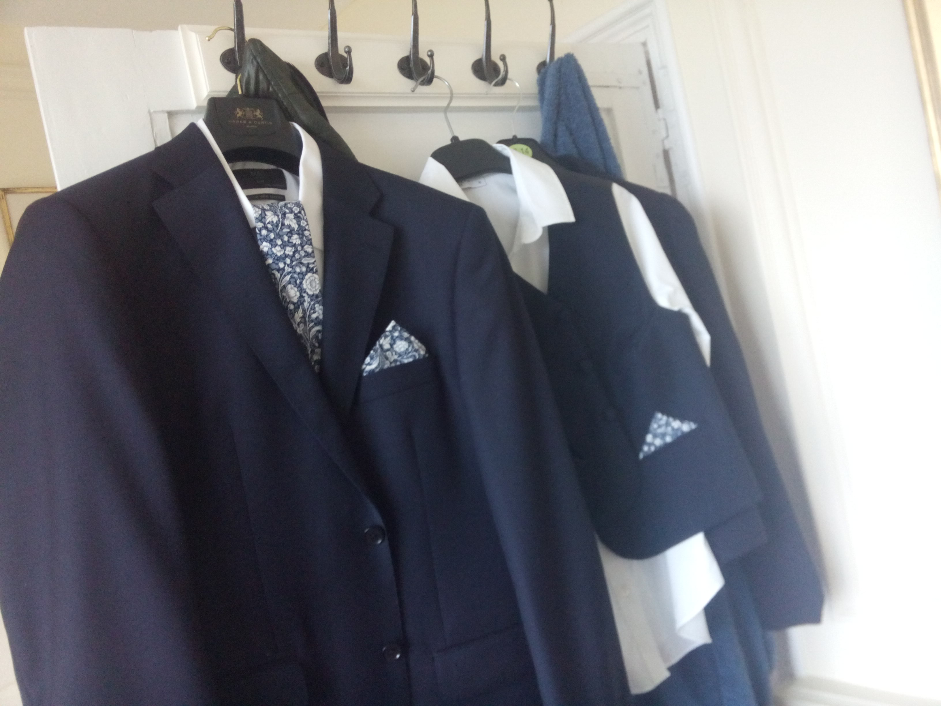 Two navy suit sets hanging on the back of a door