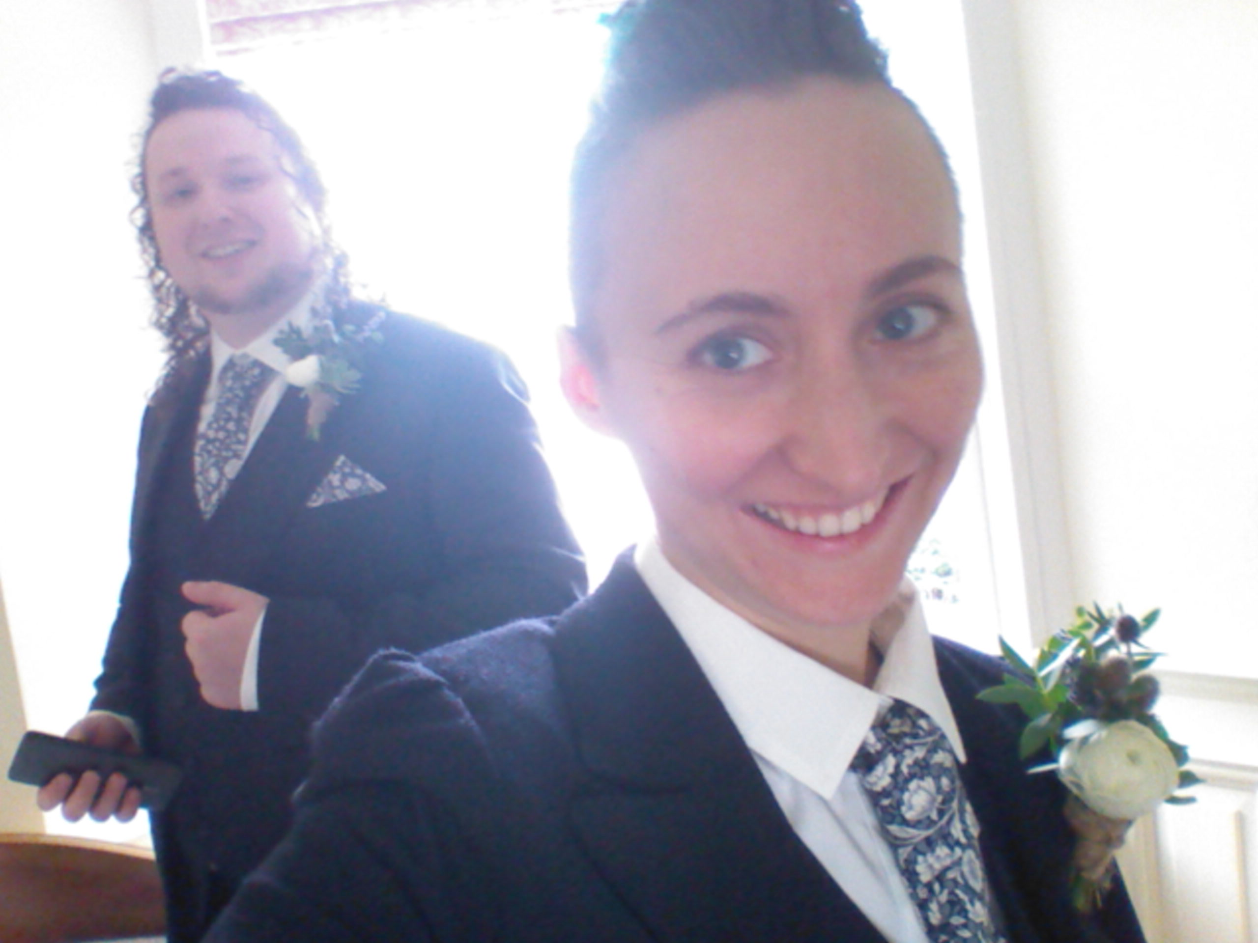 A selfie of two people in navy suits and blue and white ties with flower buttonholes and smiles